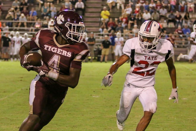 PHS' Greg Perkins (4) races toward the sideline as Tate's Jonah Smith (22) races in to tackle him during the homecoming game at Pensacola High on Friday, September 14, 2018.