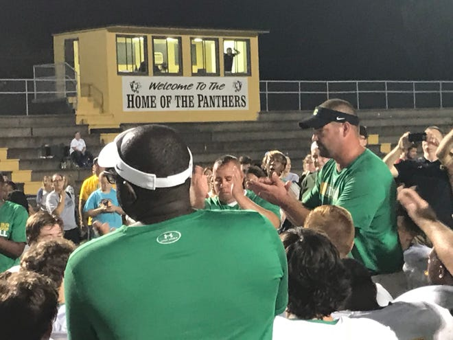 Catholic High coach Matt Adams talks to his Crusaders team after their 17-13 win Friday night on the road against Milton.