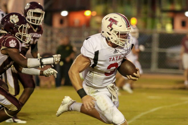 Tate quarterback Hunter Riggan keeps the ball and runs for a 20-yard touchdown against the Tigers during the homecoming game at Pensacola High School on Friday, September 14, 2018.