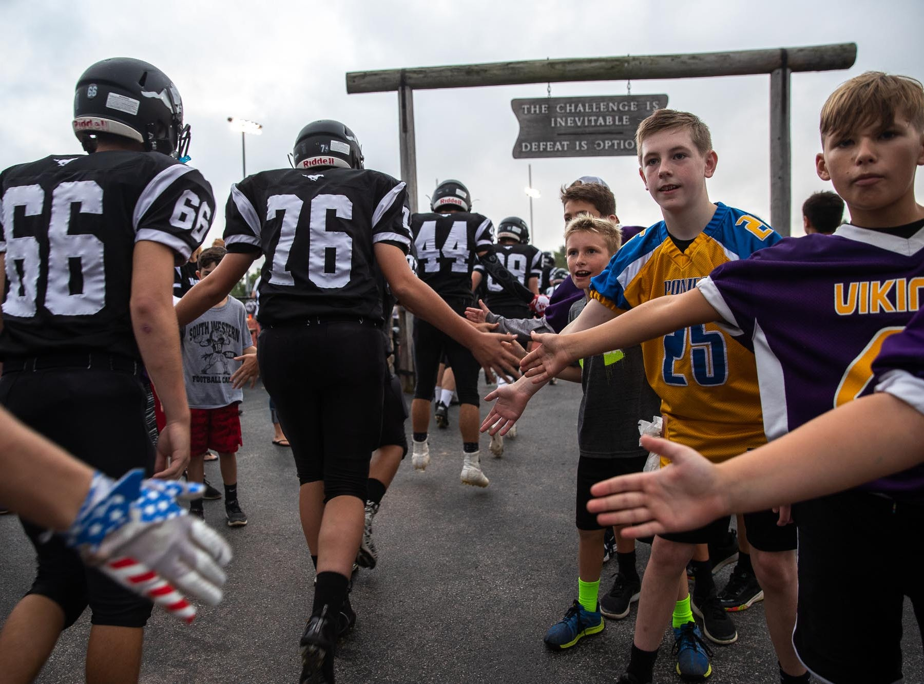 South Western players shake hands with children as they enter the field before a football game between South Western and Dallastown, Friday, Sept. 14, 2018, at South Western High School in Penn Township. Dallastown won, 35-7.