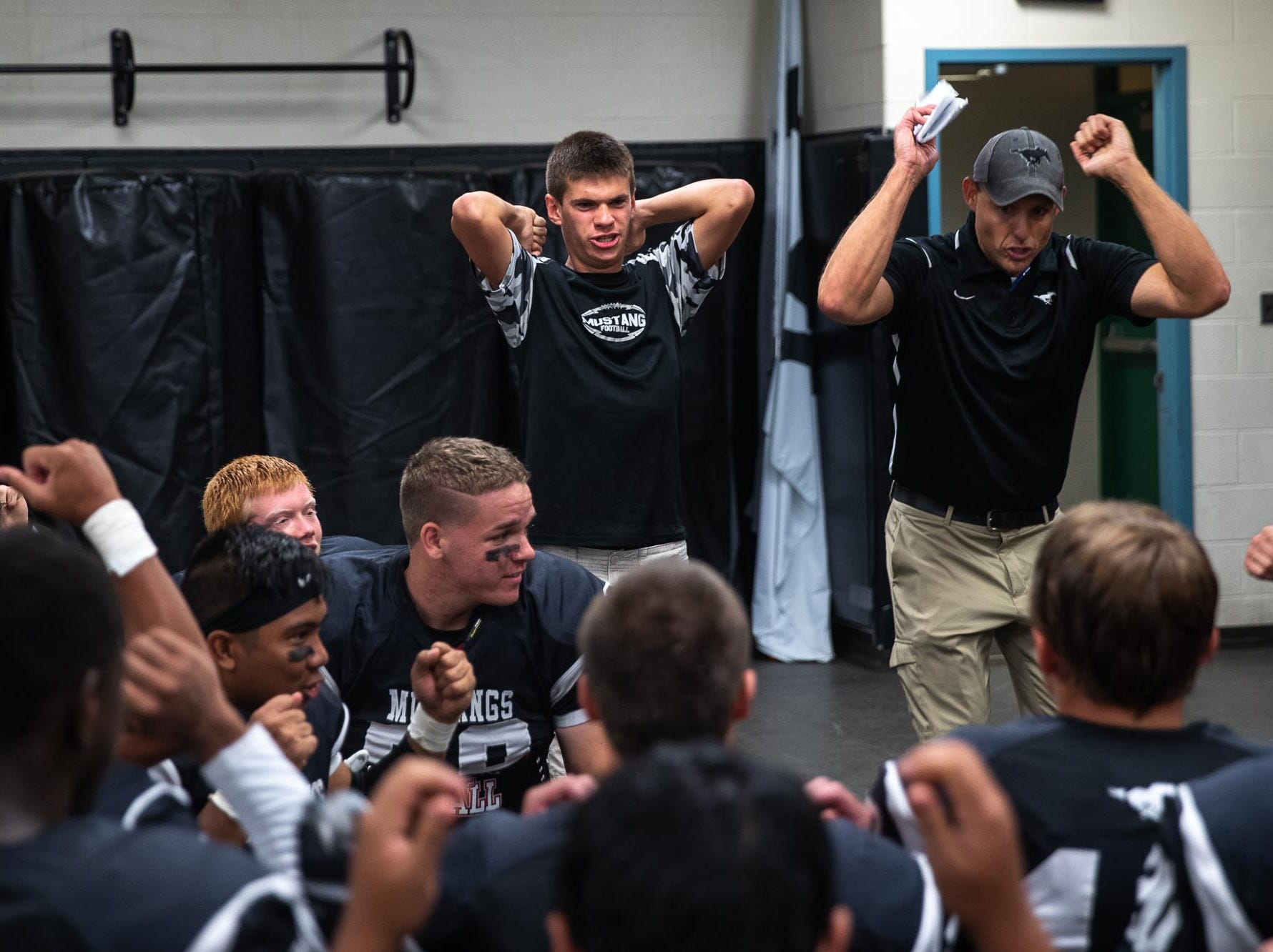 Headcoach Chris Heilman hypes up his team by pretending to ride a roller coaster in the locker room before a football game between South Western and Dallastown, Friday, Sept. 14, 2018, at South Western High School in Penn Township. Dallastown won, 35-7.