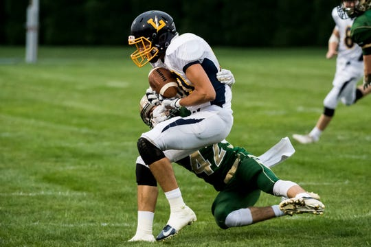 Littlestown's Jacob Thomas is tackled by York Catholic's Benjamin Moir on Friday, September 14, 2018. The Bolts fell 22-19.