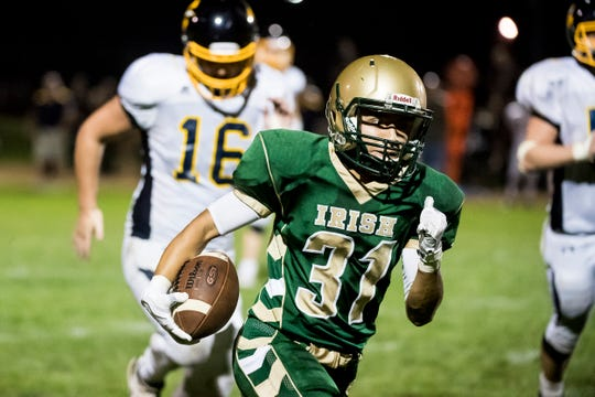 York Catholic's Manuel Montes runs with the ball after making a catch against Littlestown on Friday, September 14, 2018. The Fighting Irish won 22-19.
