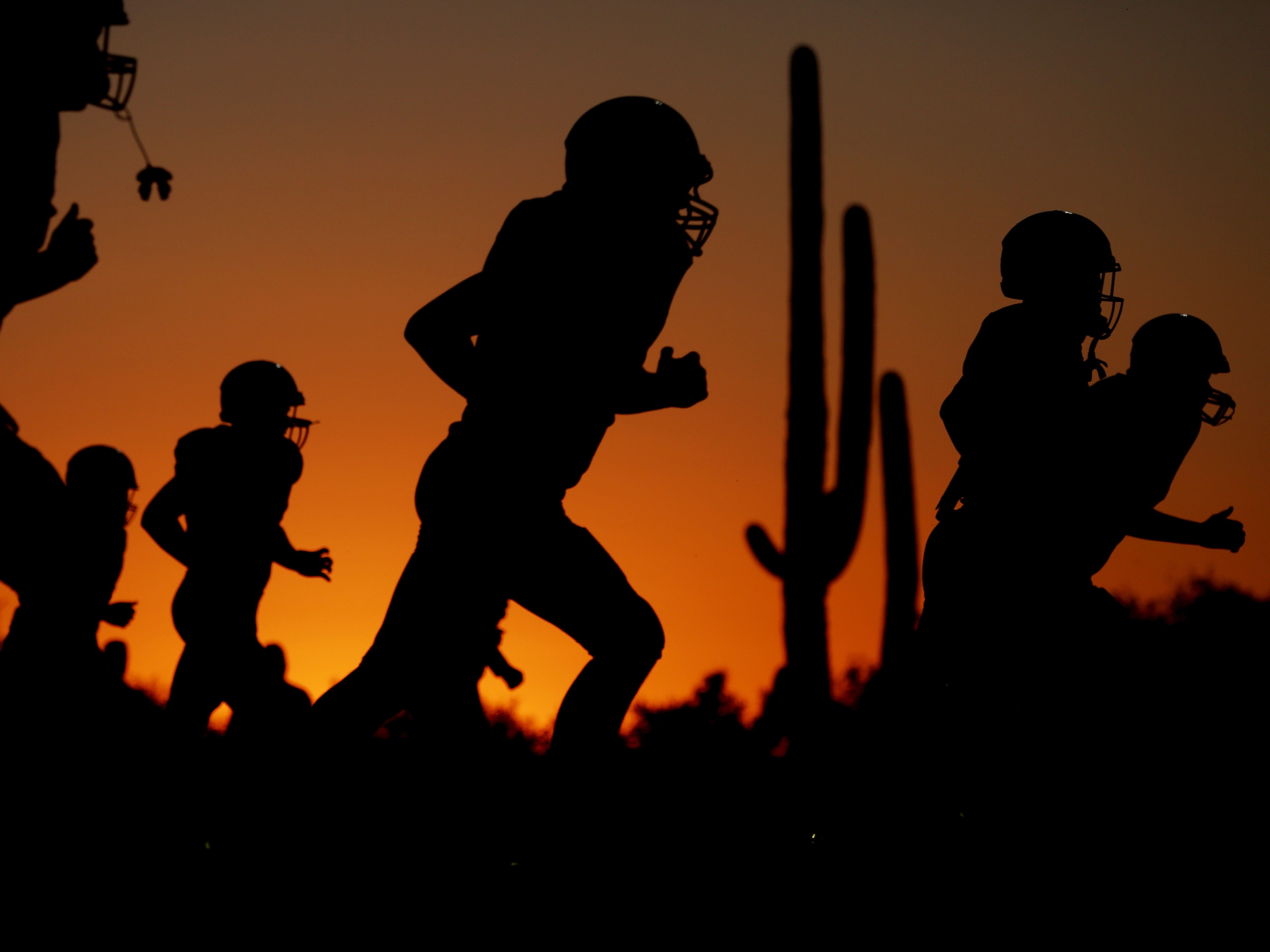 Peoria Centennial players warm up as the sun sets to the west before the Ironwood Ridge vs. Peoria Centennial high school football game at Ironwood Ridge High School, 2475 W. Naranja Drive, on Sept. 14, 2018, in Oro Valley, Ariz. Centennial won 55-7.