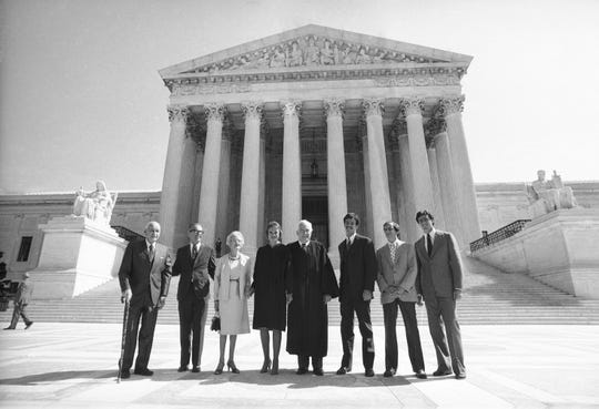 Justice Sandra Day O'Connor poses for photos on the steps of the Supreme Court before being sworn in with her family on Sept. 26, 1981. From left are: Justice O'Connor's father, Harry Day; her husband, John J. O'Connor; her mother, Ada Mae Day; O'Connor; Chief Justice Warren Burger; and her sons, Brian, Jay and Scott.