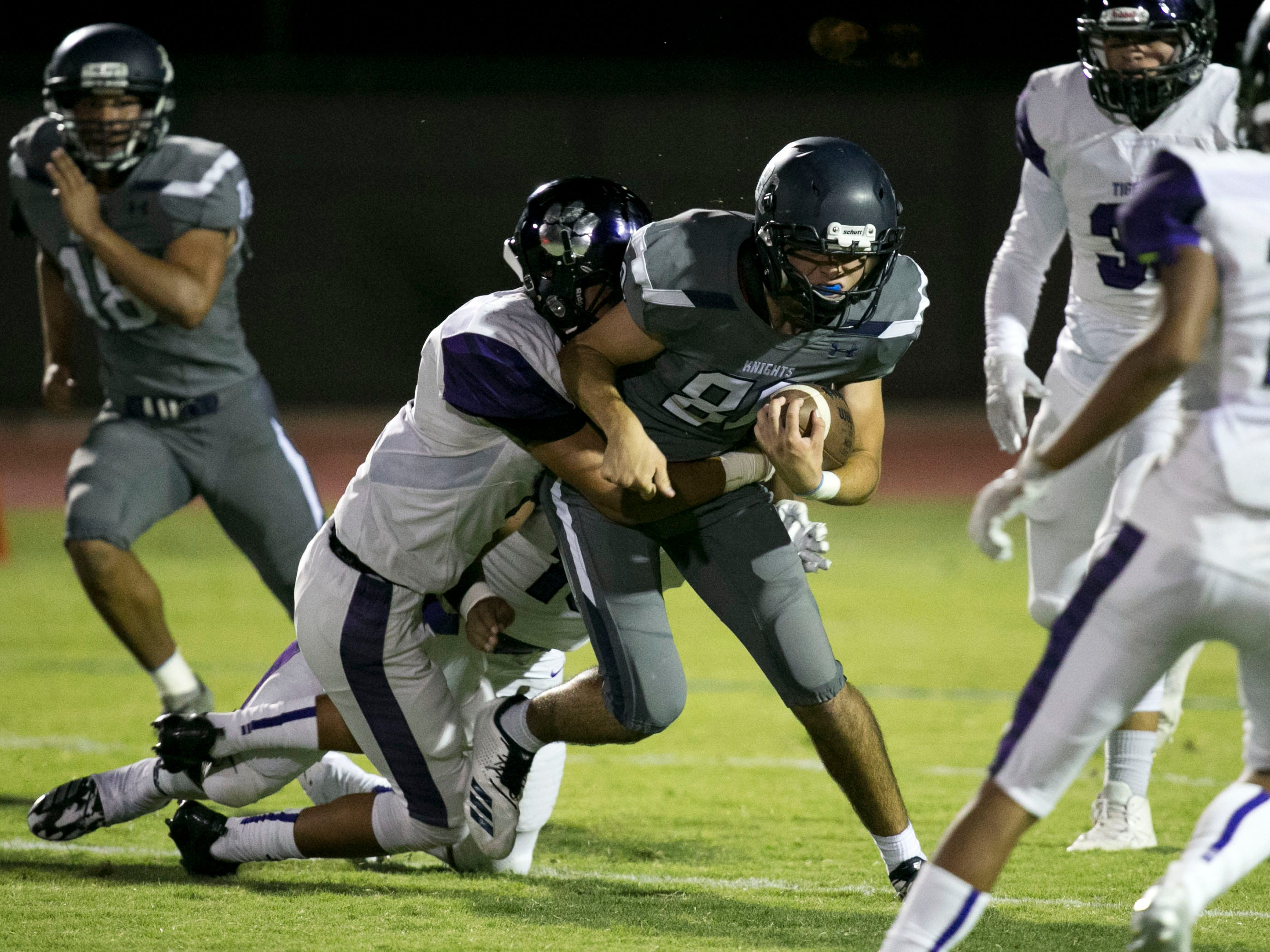Higley High receiver Jaxen Gibbons is tackled by a Millennium High defender during the first quarter of the high school football game at Higley High in Gilbert on Friday evening, September 14, 2018.