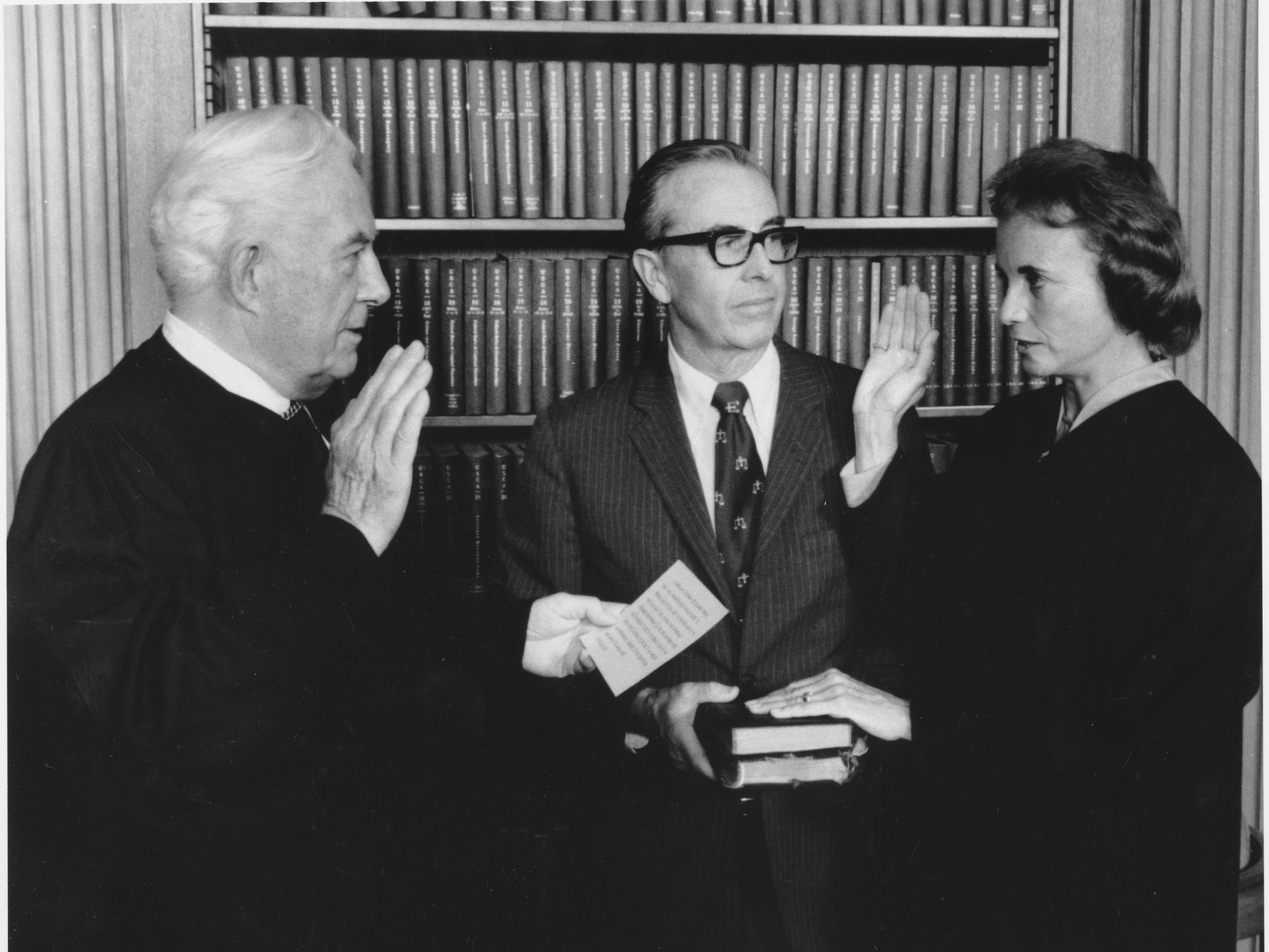 Sandra Day O'Connor is sworn in as an Associate Justice by Chief Justice Warren Burger at the Supreme Court in Washington, D.C. on Friday, Sept. 25, 1981.  Holding two family bibles, at center, is husband John J. O'Connor.
