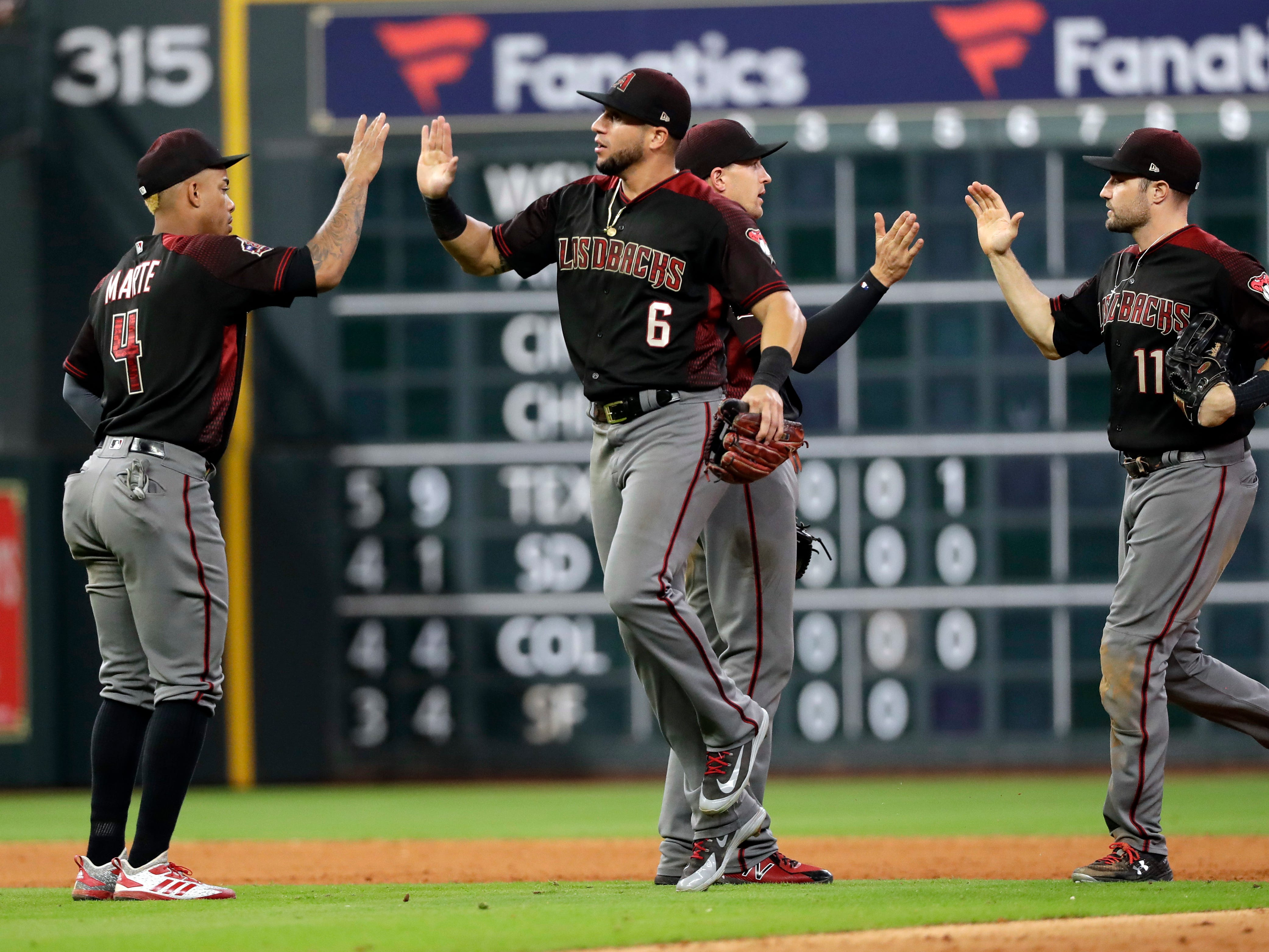 Arizona Diamondbacks' Ketel Marte (4), David Peralta (6), Nick Ahmed and A.J. Pollock (11) celebrate after a baseball game against the Houston Astros Friday, Sept. 14, 2018, in Houston. The Diamondbacks won 4-2. (AP Photo/David J. Phillip)