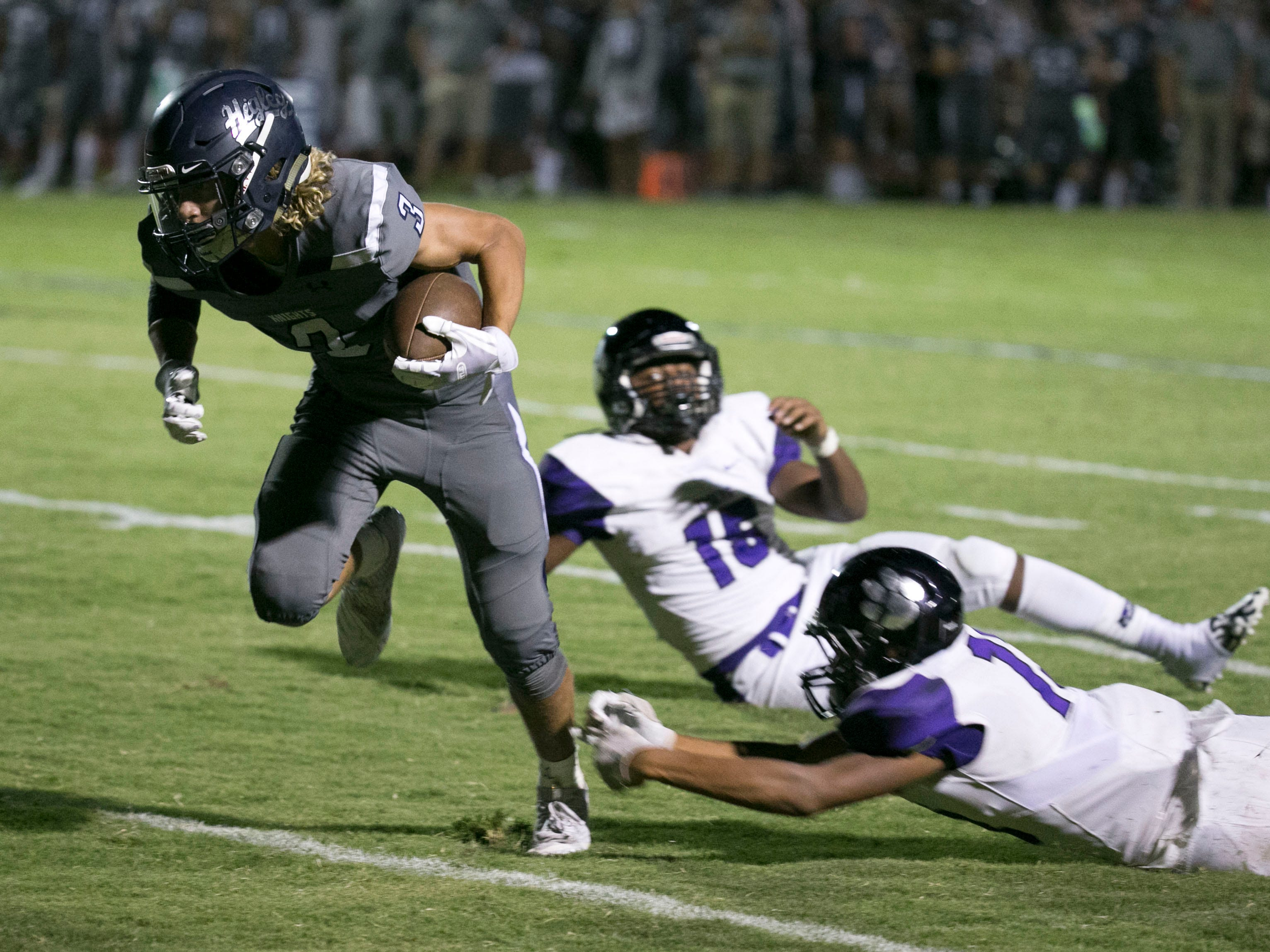 Higley High receiver Coleman Owen carries the ball past  Millennium High tacklers on his way to a touchdown during the third quarter of the high school football game at Higley High in Gilbert on Friday evening, September 14, 2018.