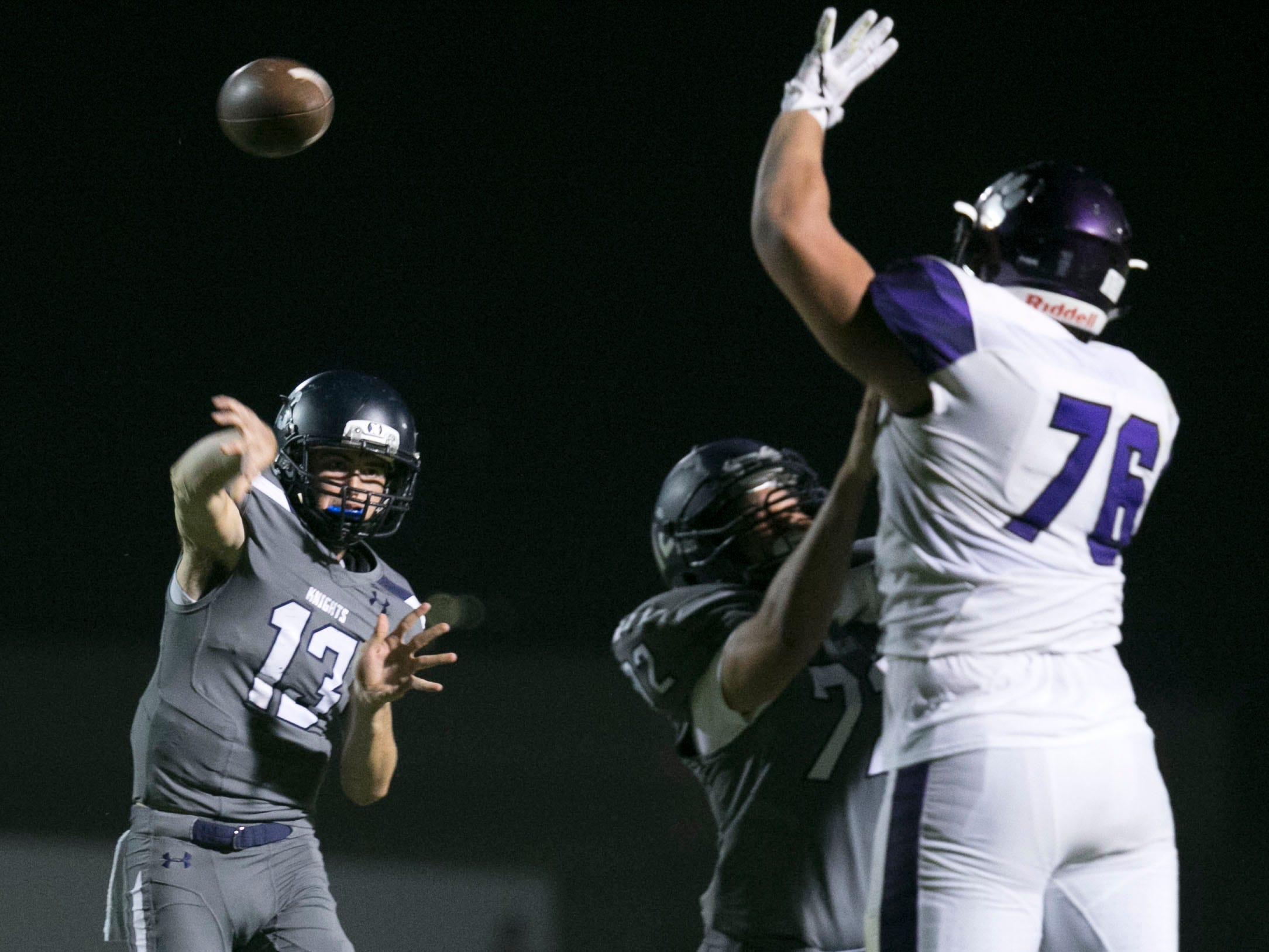 Higley High quarterback Spencer Brasch passes as Millennium High defensive lineman Anthonie Cooper attempts to block the pass during the third quarter of the high school football game at Higley High in Gilbert on Friday evening, September 14, 2018.