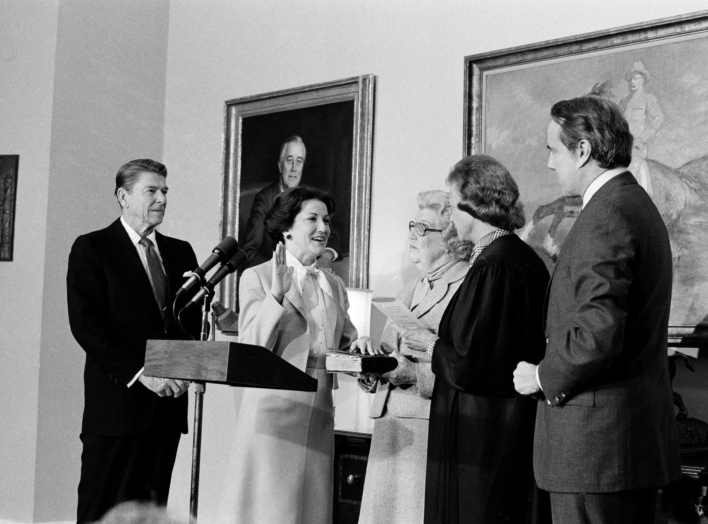 Supreme Court Justice Sandra Day O'Connor swears in Elizabeth Dole as the new Transportation Secretary, as President Reagan looks on at left, in an East Room ceremony at the White House, Feb. 7, 1983.  At far right is the husband of the secretary, Sen. Robert Dole, R-Kan., and at center is her mother, Mary Hanford.