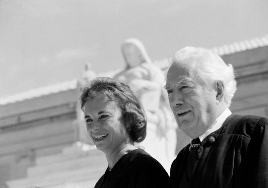 Sandra Day O'Connor and Chief Justice Warren Burger pose for pictures at the U.S. Supreme Court building in Washington, Sept. 25, 1981.