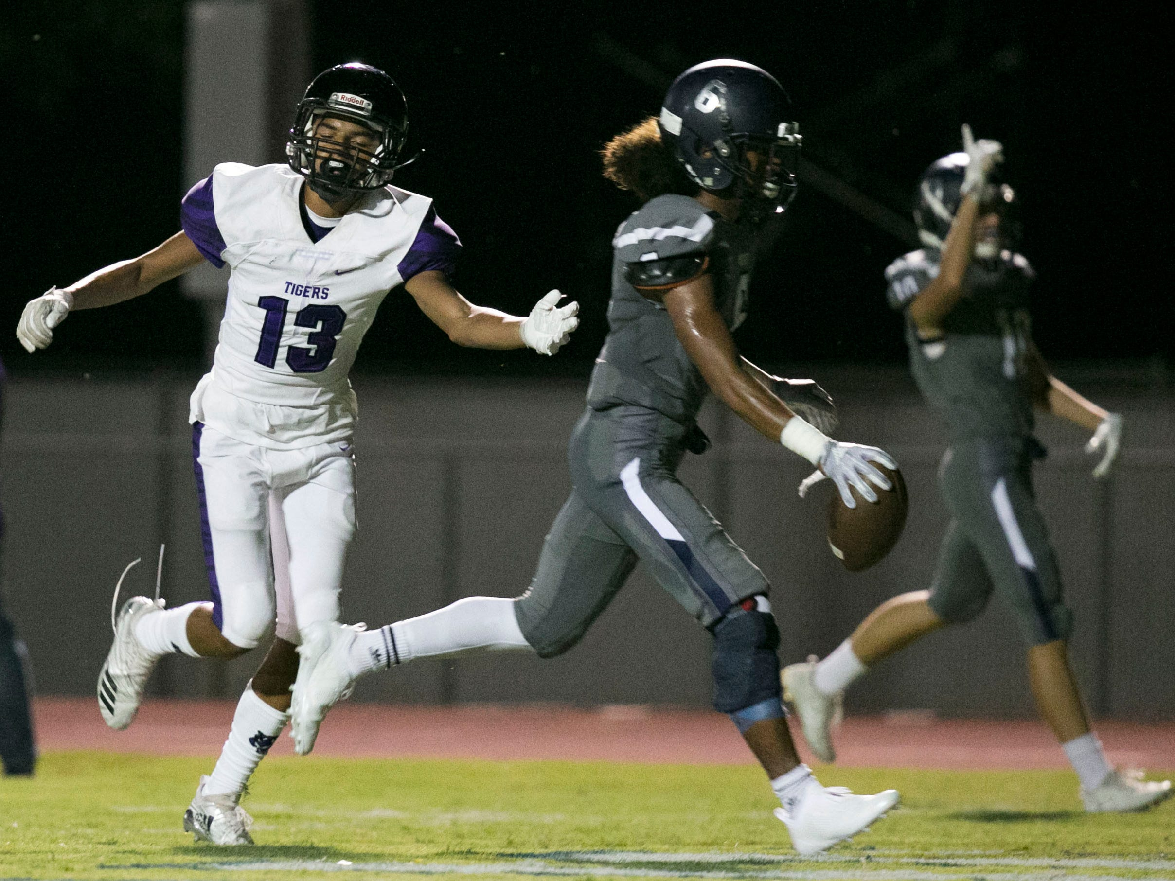 Higley High receiver James Mageo scores a touchdown past  Millennium High's Treydan Stukes during the second quarter of the high school football game at Higley High in Gilbert on Friday evening, September 14, 2018.
