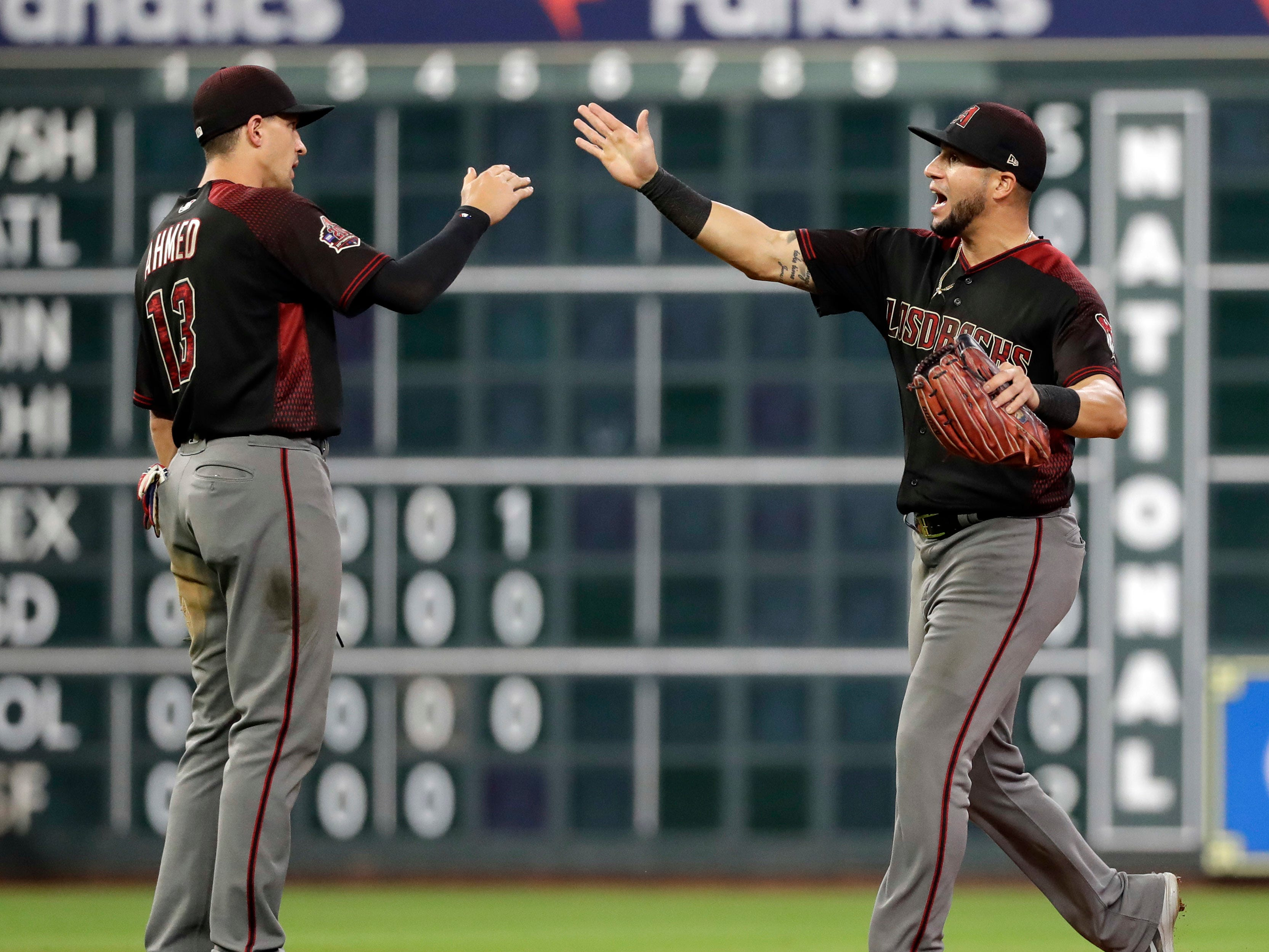 Arizona Diamondbacks' Nick Ahmed (13) and David Peralta celebrate after a baseball game against the Houston Astros Friday, Sept. 14, 2018, in Houston. The Diamondbacks won 4-2. (AP Photo/David J. Phillip)