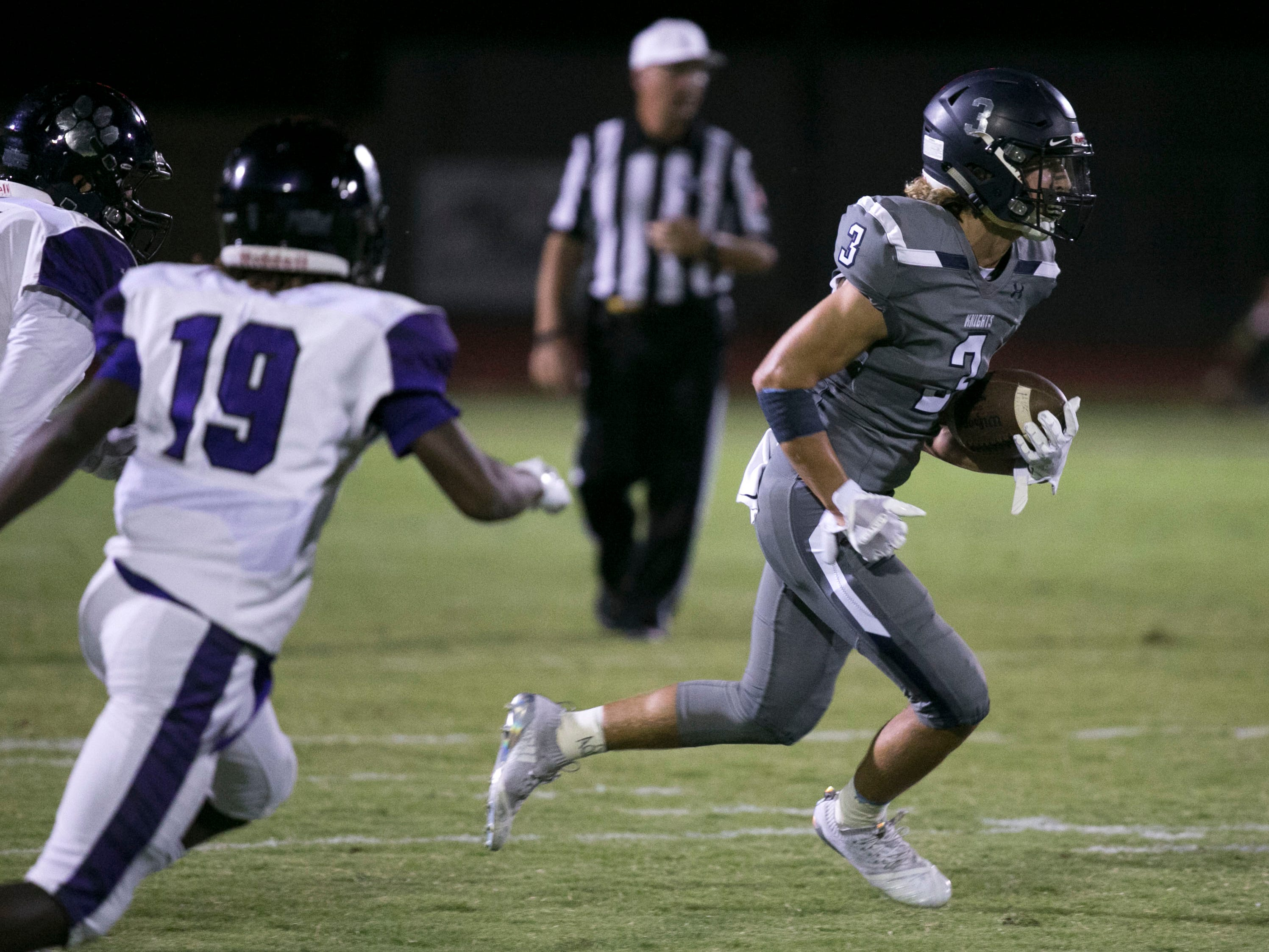 Higley High receiver Coleman Owen carries the ball as he is pursued by Millennium High defensive back Kaysan Barnett during the second quarter of the high school football game at Higley High in Gilbert on Friday evening, September 14, 2018.