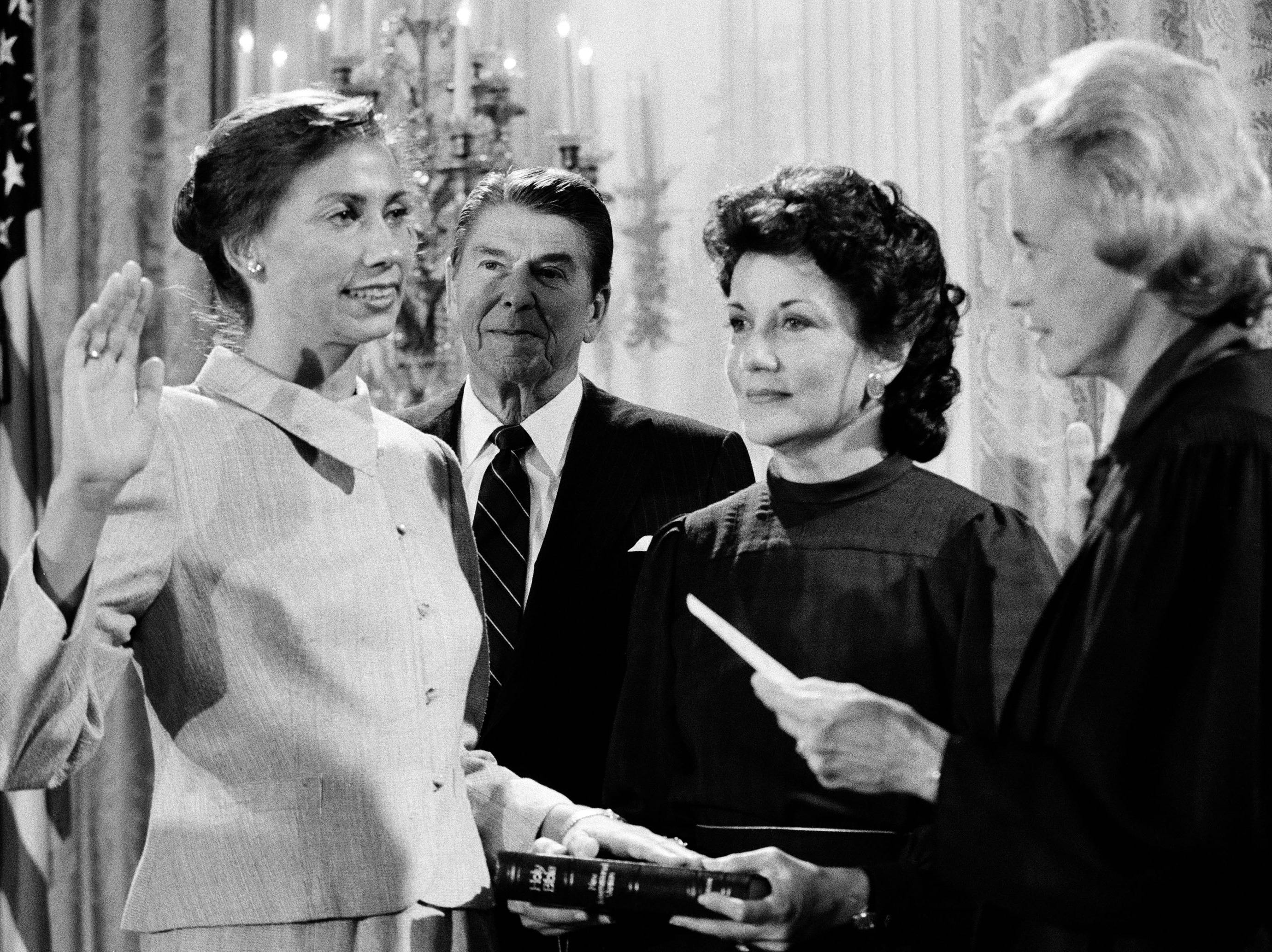 President Ronald Reagan watches as Supreme Court Justice Sandra Day O'Connor, right, swears in Barbara McConnell, left, as a member of the Civil Aeronautics Board at the White House, Sept. 23, 1983.  Transportation Secretary Elizabeth Dole holds the bible as McConnell is sworn in.