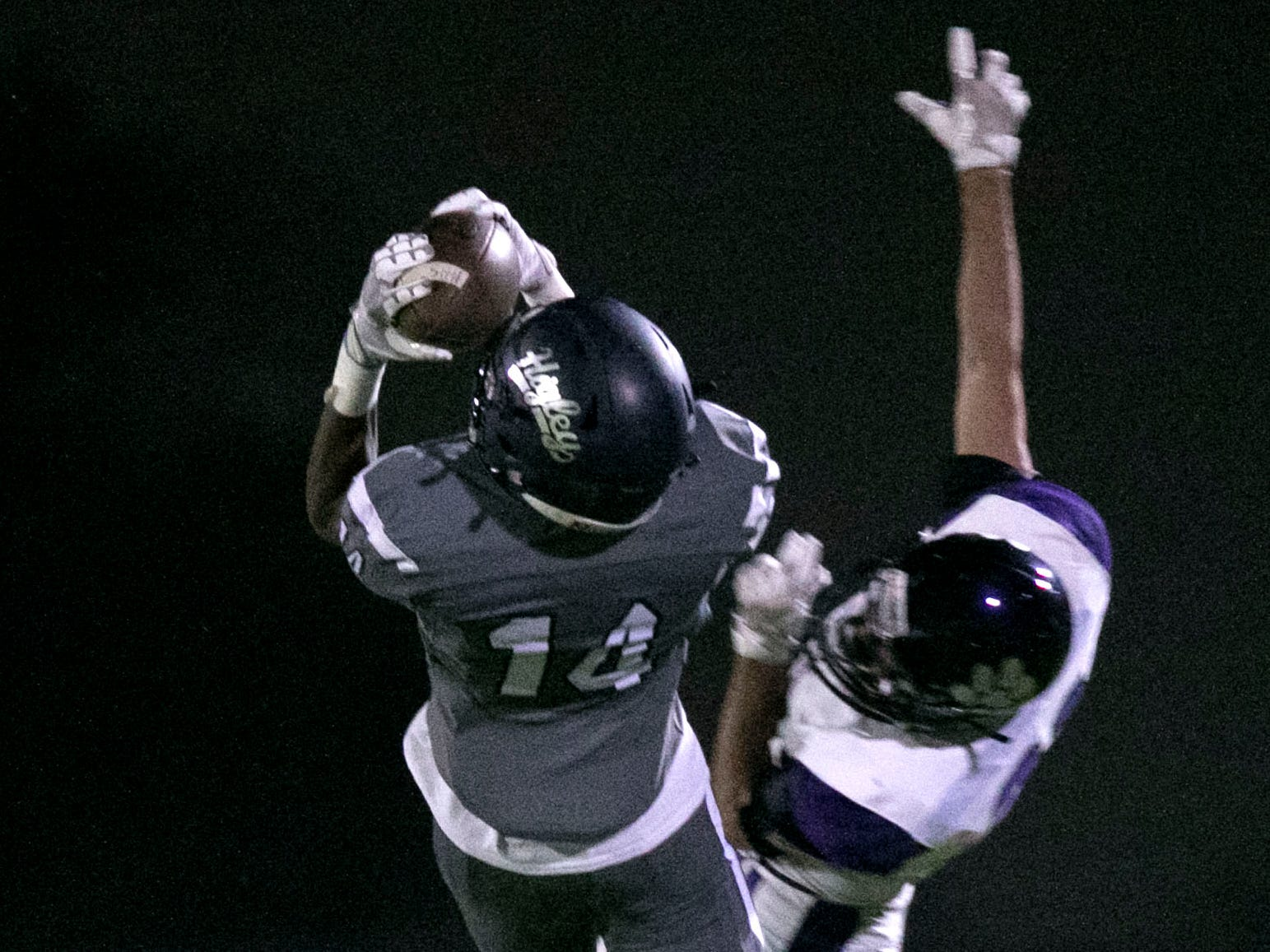 Higley High receiver Logan Mack catches a pass over Millennium High defensive back Nico Montejo during the third quarter of the high school football game at Higley High in Gilbert on Friday evening, September 14, 2018.