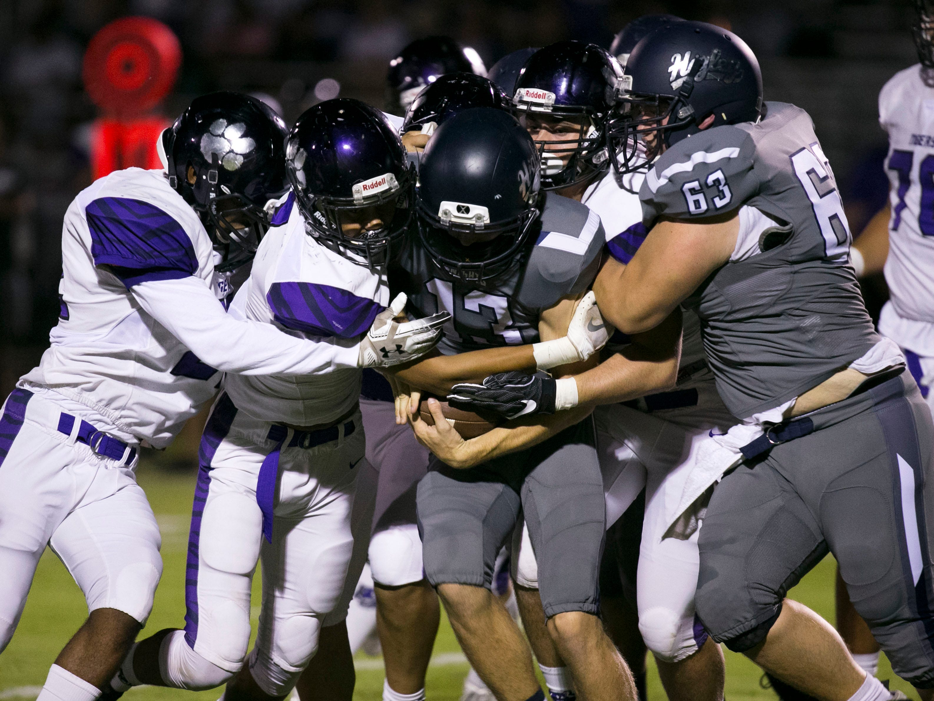 Higley High quarterback Spencer Brasch is tackled by a host of Millennium High defenders as Brasch gets a push from teammate Daniel McWilliams during the first quarter of the high school football game at Higley High in Gilbert on Friday evening, September 14, 2018.