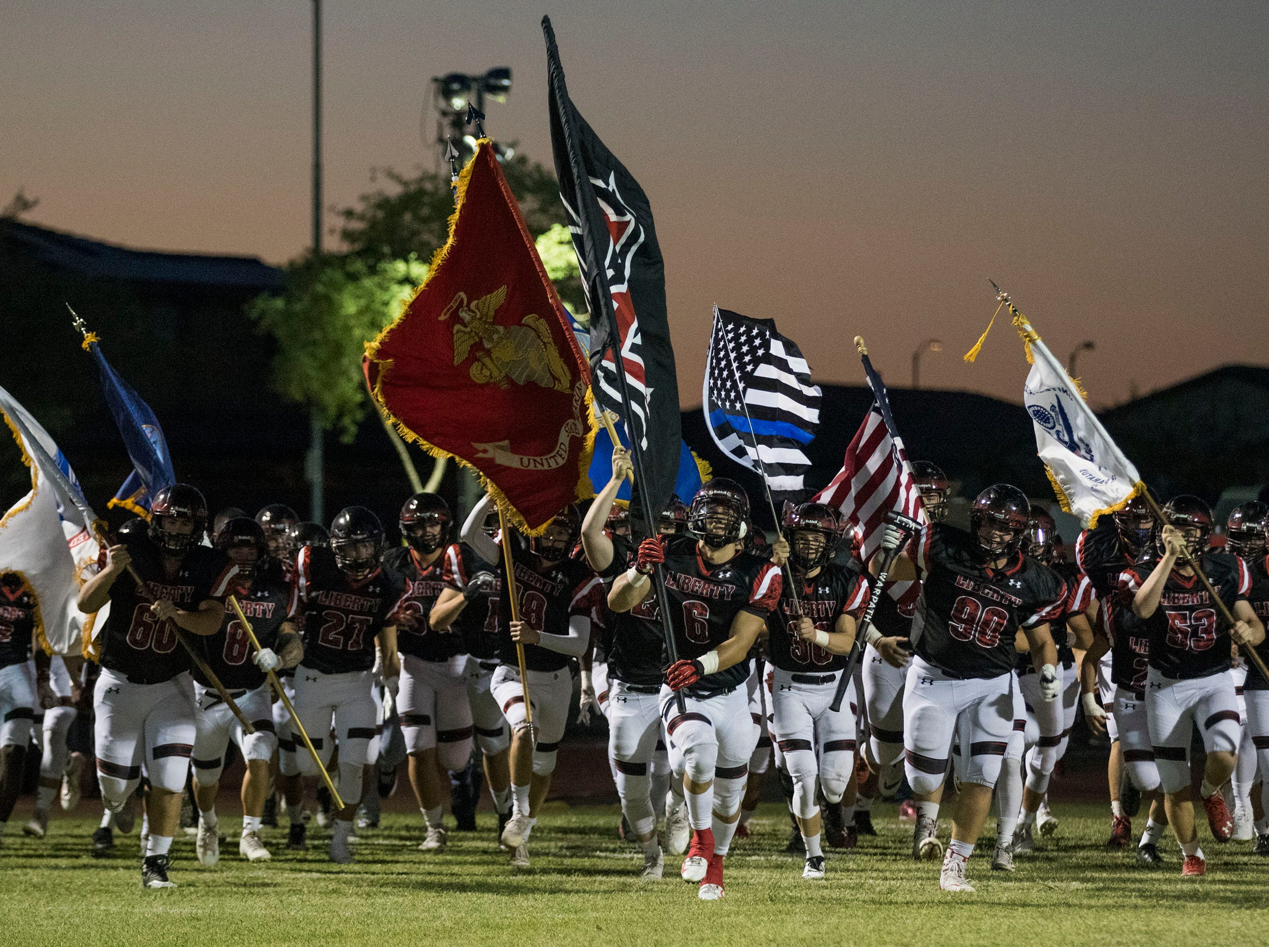 Honoring the different branches of the military Liberty players carry flags out onto the field before their game with Leland (CA) in Peoria Friday, Sept.14, 2018. #azhsfb