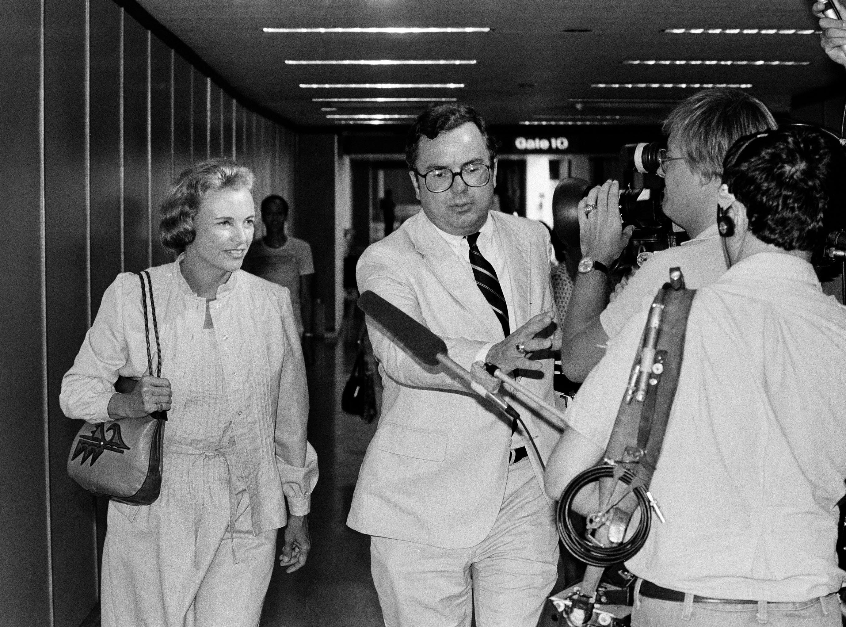 A unidentified White House aide clears a path through cameramen for Supreme Court nominee Sandra Day O'Connor, left, on her arrival at Washington National Airport, July 13, 1981.