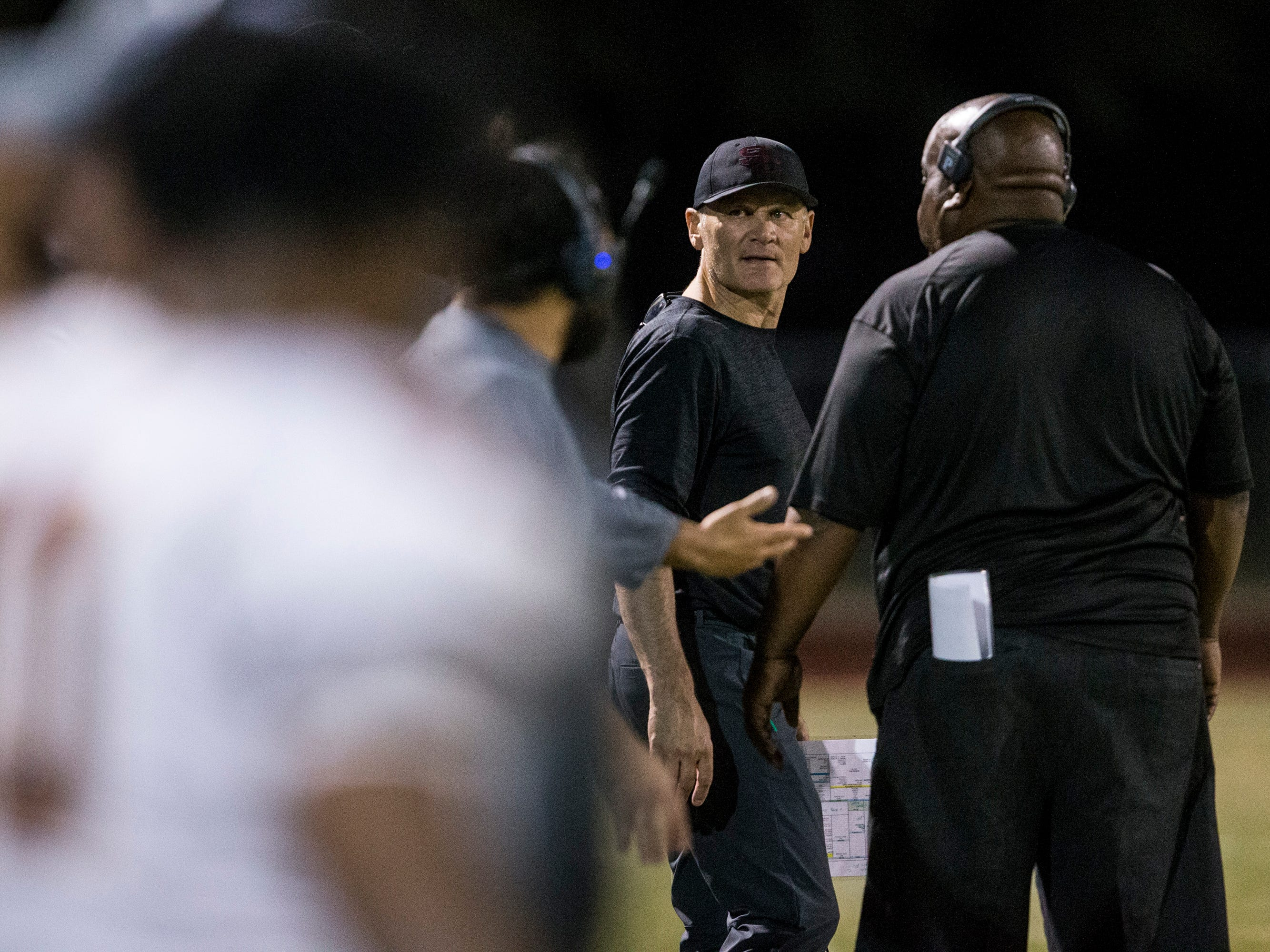 Salpointe head coach Dennis Bene talks to coaches during the game against Cactus on Friday, Sept. 14, 2018, at Cactus High School in Glendale, Ariz.