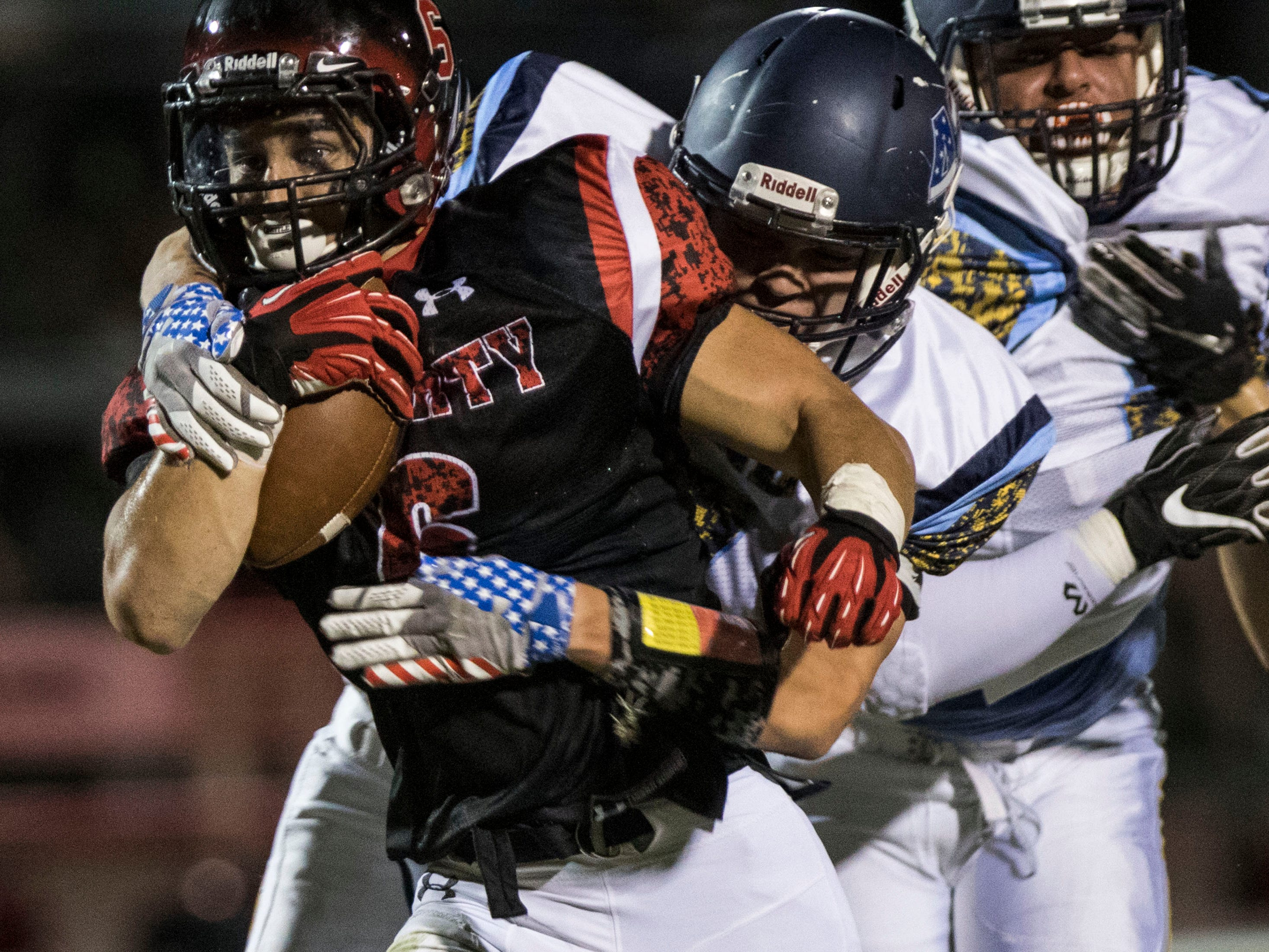 Liberty's Jett Kinsch gets wrapped up by Leland's Preston Gook during their game in Peoria Friday, Sept.14, 2018. #azhsfb