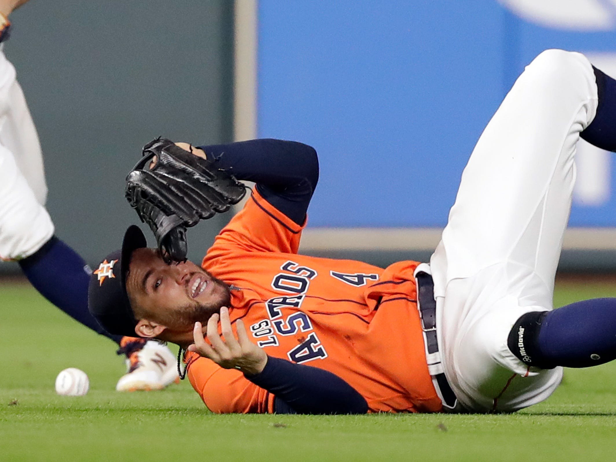 Houston Astros center fielder George Springer (4) tumbles while trying to catch a single by Arizona Diamondbacks' A.J. Pollock during the eighth inning of a baseball game Friday, Sept. 14, 2018, in Houston. Pollock was out at second trying to stretch his hit into a double. (AP Photo/David J. Phillip)