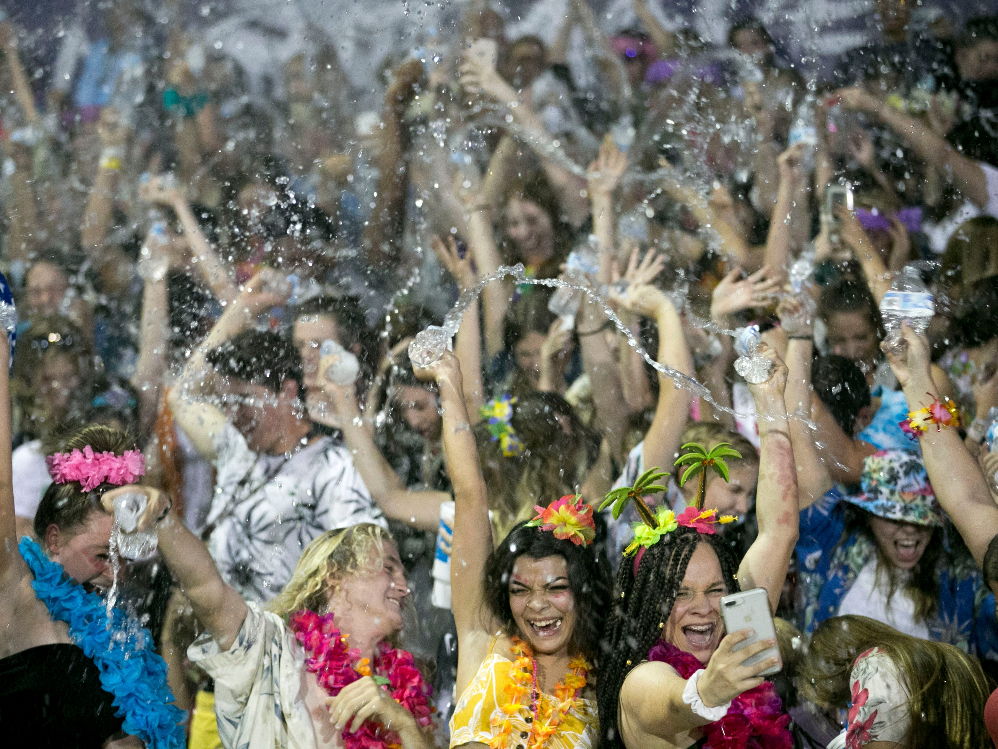 The Higley High student section cheers and splashes bottled water around during kickoff at the start of the high school football game between Millennium and Higley High at Higley High in Gilbert on Friday evening, September 14, 2018.