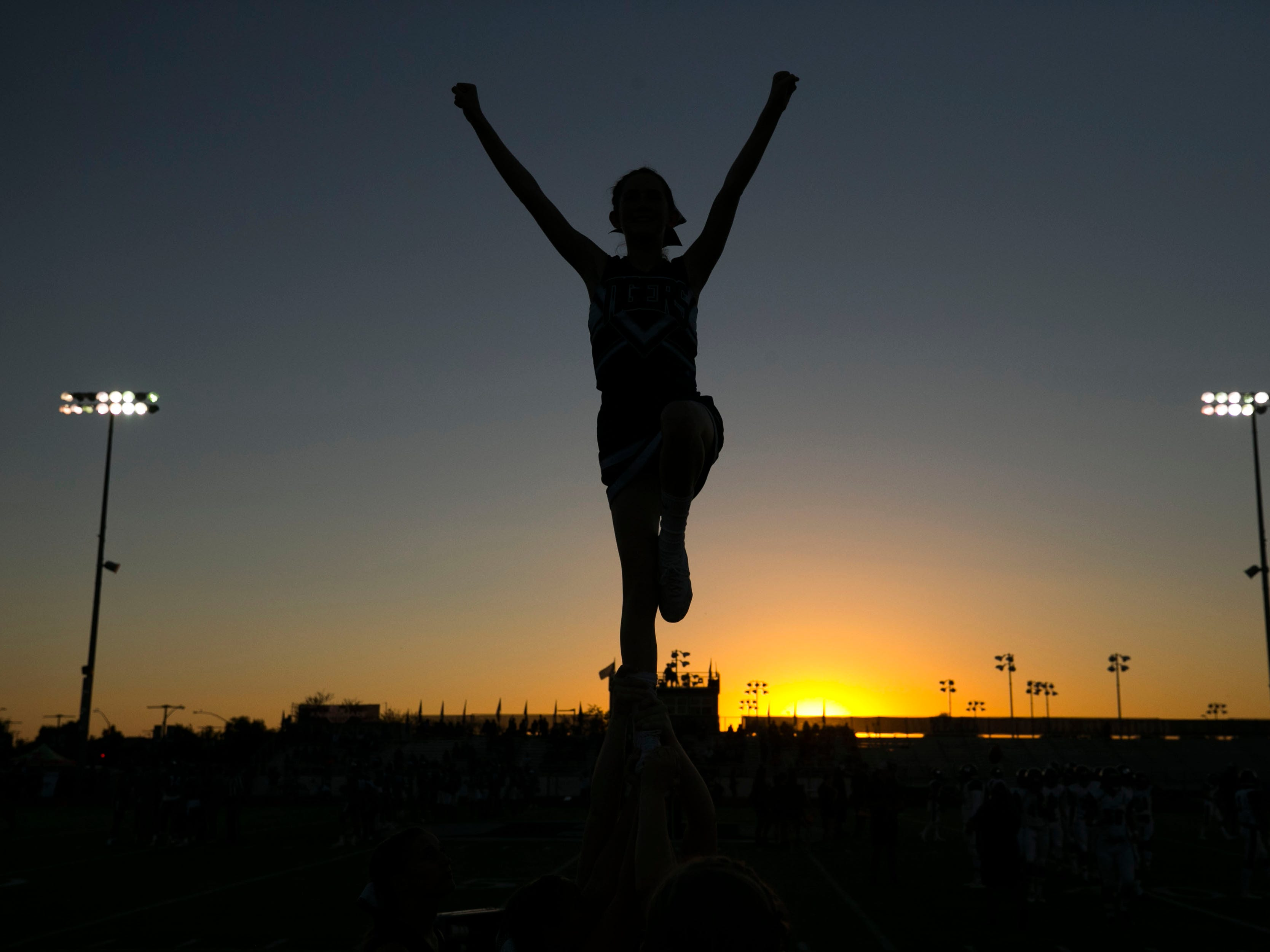 Millennium High cheers perform stunts before the high school football game between Millennium and Higley High at Higley High in Gilbert on Friday evening, September 14, 2018.