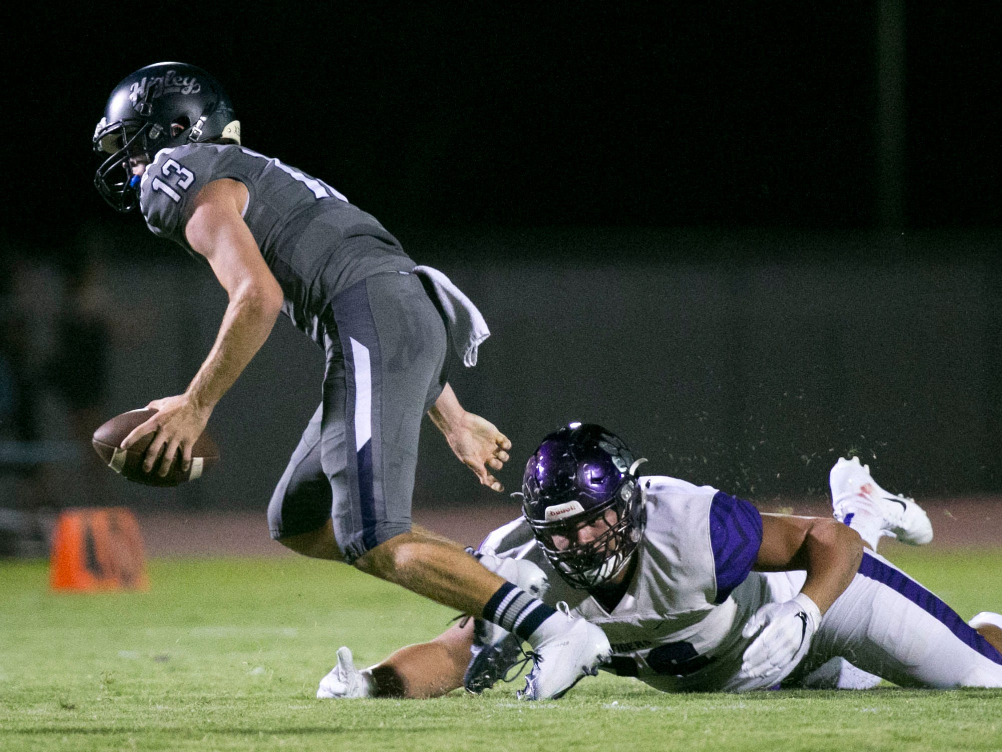 Higley High quarterback Spencer Brasch escapes the grasp of Millennium High defensive lineman Anthonie Cooper during the first quarter of the high school football game at Higley High in Gilbert on Friday evening, September 14, 2018.