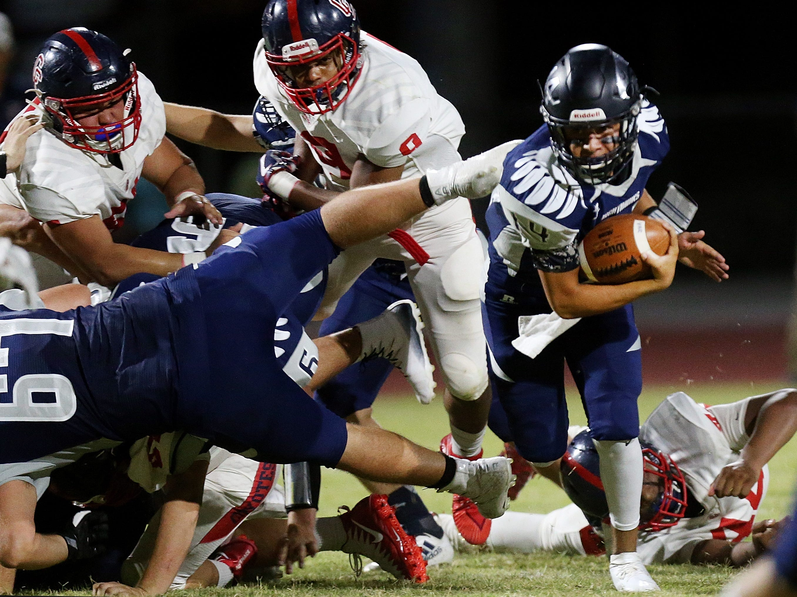 Ironwood Ridge quarterback Fabian Figueroa (14) breaks through the melee for a keeper during the second quarter of the Ironwood Ridge vs. Peoria Centennial high school football game at Ironwood Ridge High School, 2475 W. Naranja Drive, on Sept. 14, 2018, in Oro Valley, Ariz. Centennial won 55-7.