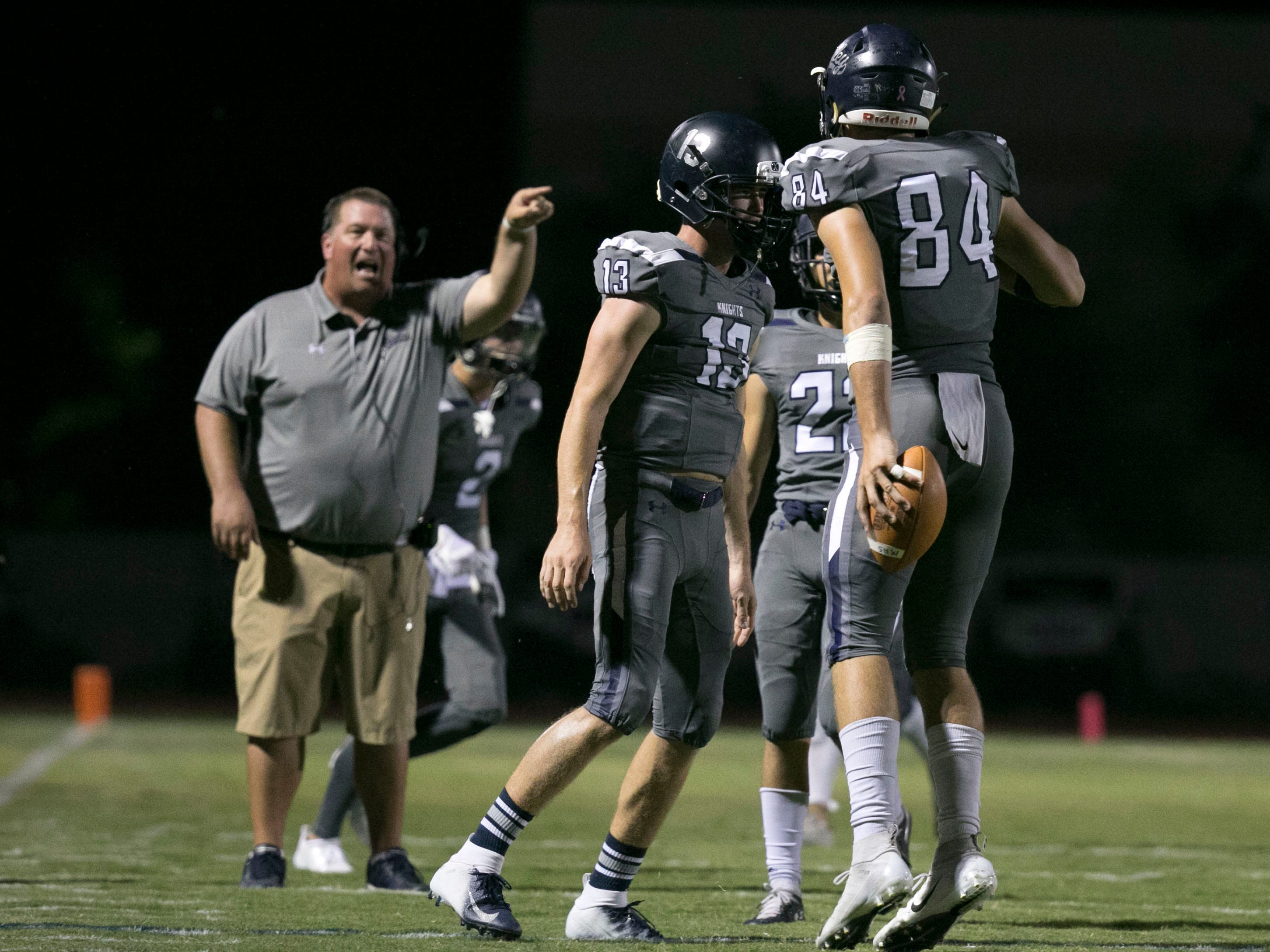 Higley High's Logan Maxwell celebrates after scoring a touchdown after blocking a punt on Millennium High during the second quarter of the high school football game at Higley High in Gilbert on Friday evening, September 14, 2018. Higley High head football coach Eddy Zubey (background) yells for the celebration to end.