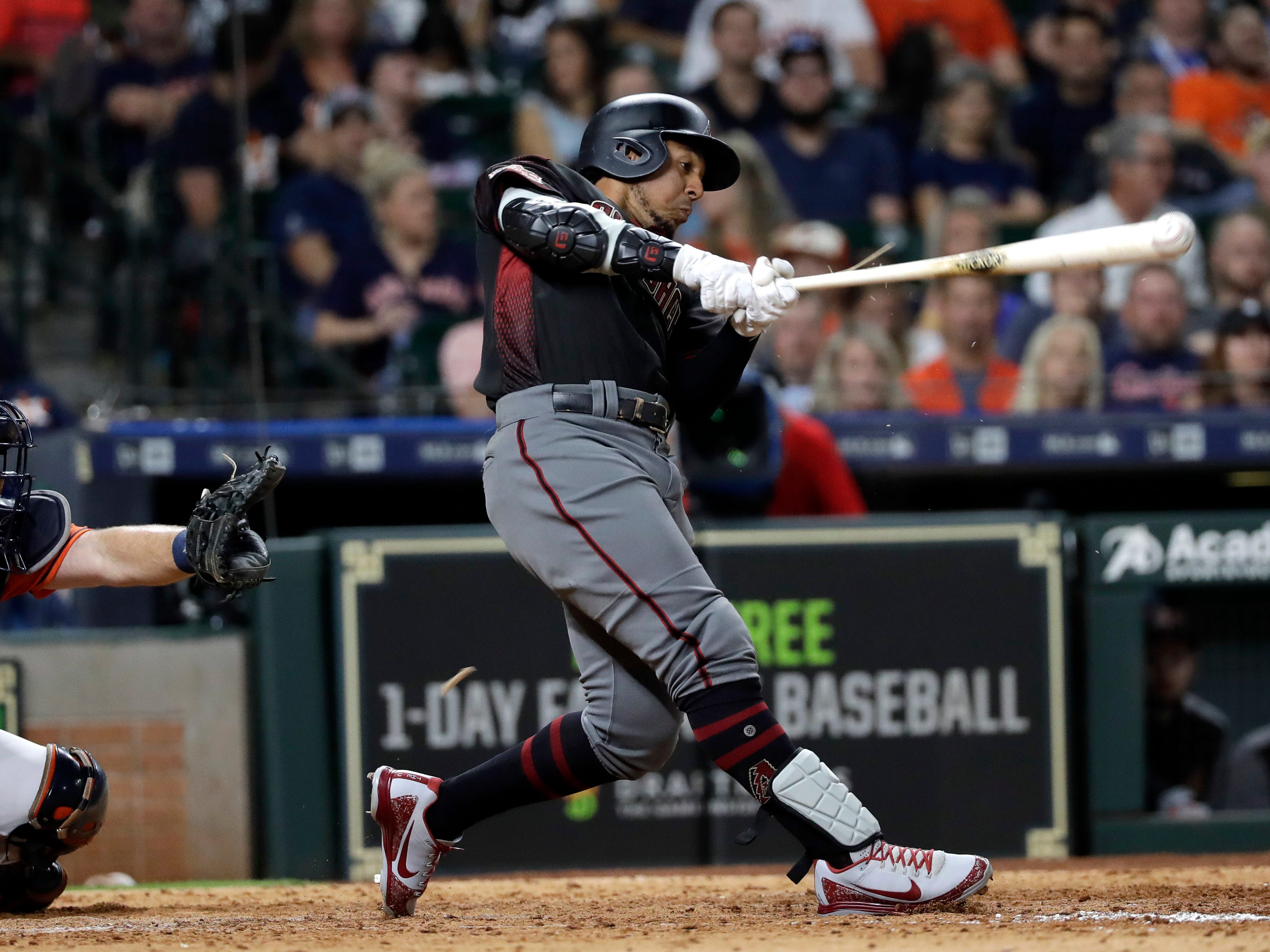 Arizona Diamondbacks' Jon Jay, right, hits a triple to score Nick Ahmed as Houston Astros catcher Brian McCann reaches for the pitch during the eighth inning of a baseball game Friday, Sept. 14, 2018, in Houston.
