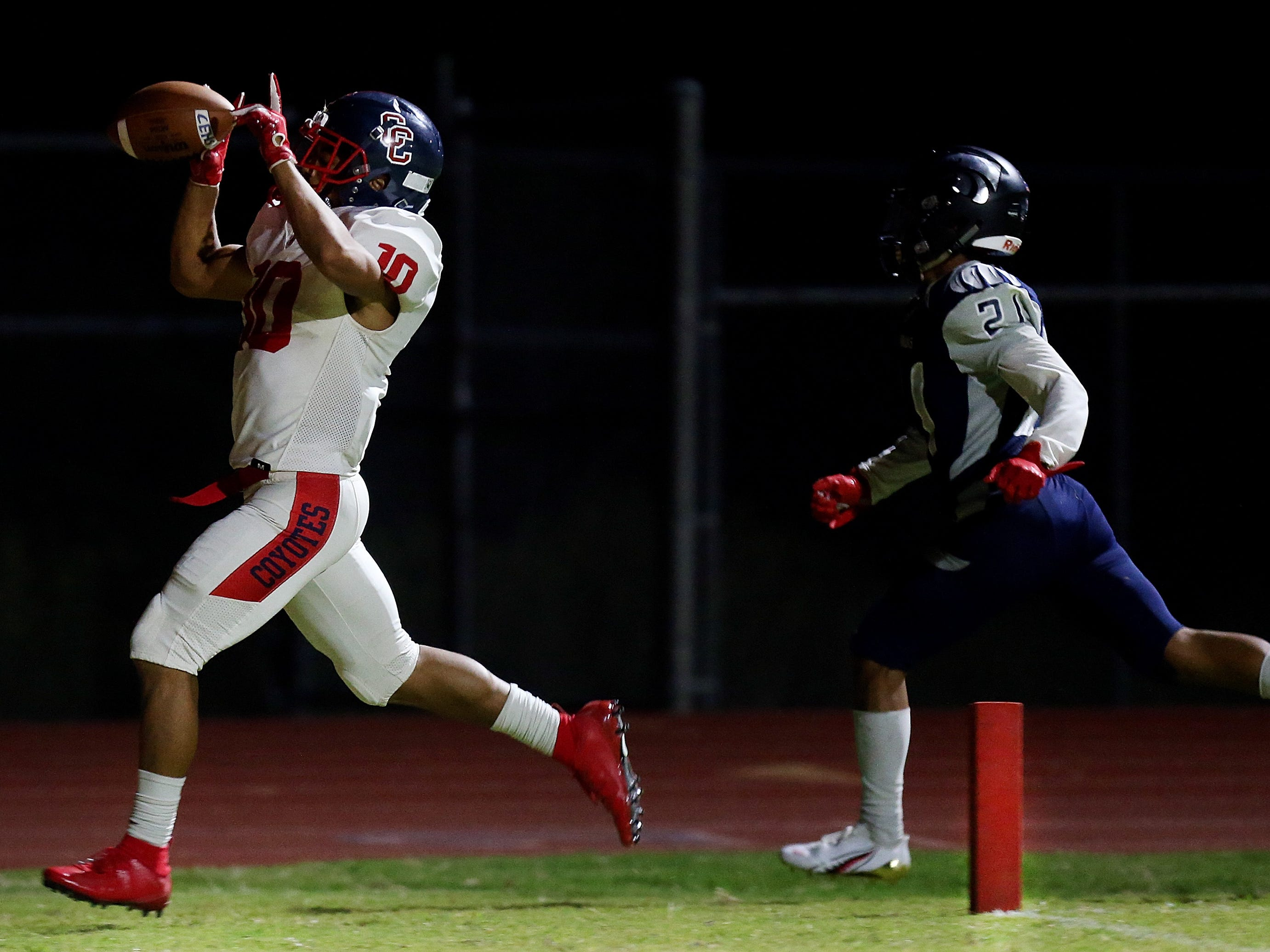 Peoria Centennial's Jeiel Stark (10) motions skyward after a touchdown score ahead of Ironwood Ridge defensive back Daniel Aguirre (21) during the third quarter of the Ironwood Ridge vs. Peoria Centennial high school football game at Ironwood Ridge High School, 2475 W. Naranja Drive, on Sept. 14, 2018, in Oro Valley, Ariz. Centennial won 55-7.