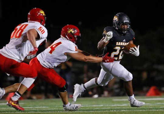 Saguaro's Israel Benjamin (22) runs through a tackle from Chaparral's Zien Tessler (54) at Saguaro High School in Scottsdale, Ariz. on Sept. 14, 2018.