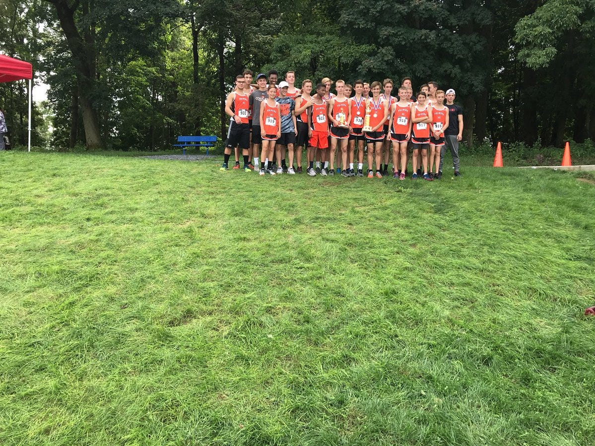 The Palmyra boys cross country team poses with their team championship trophy at the Lebanon County meet on Saturday.