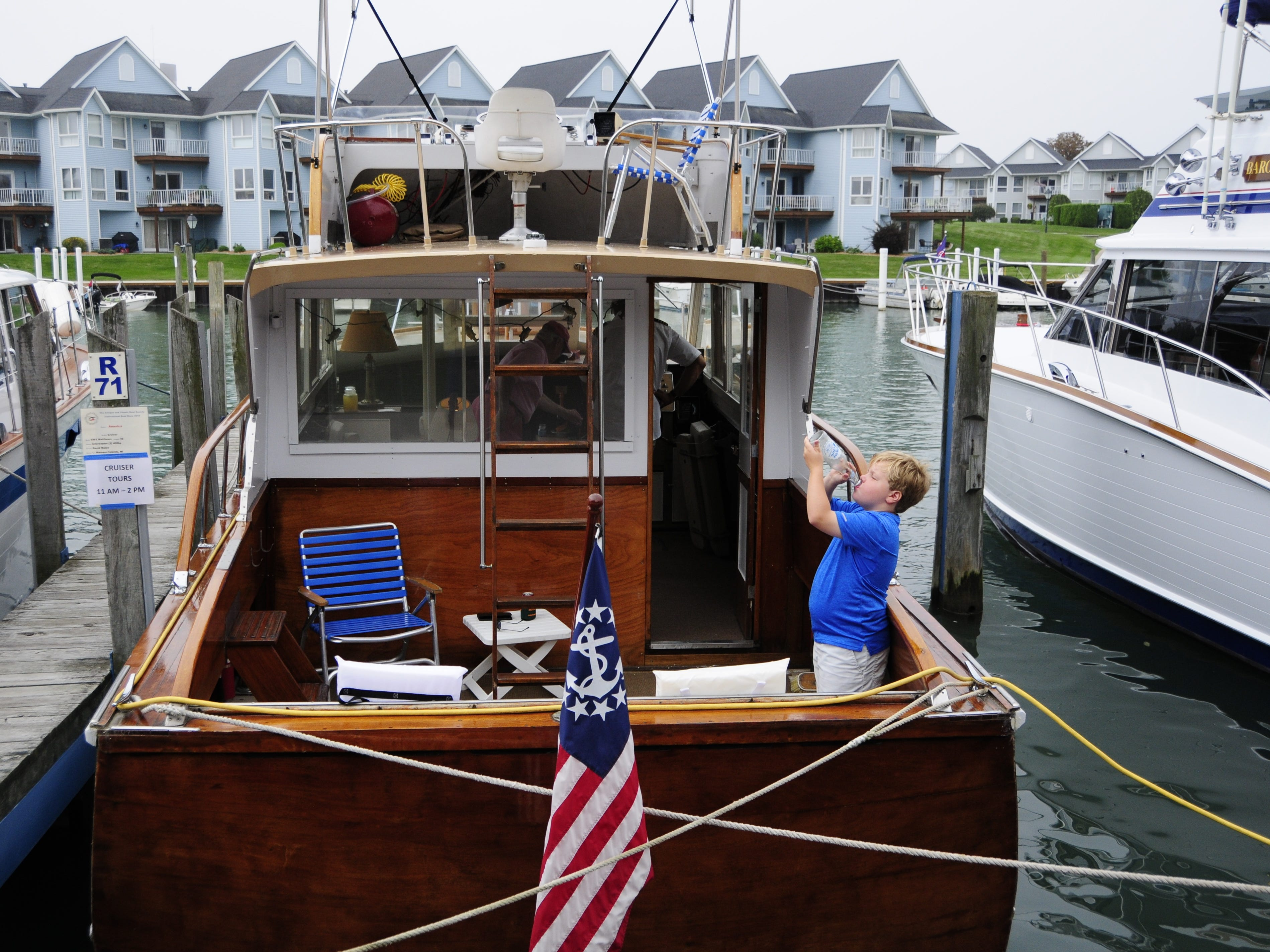 Mason Halsey drinks a soda in the stern of the America during the Antique and Classic Boat Society International Boat Show on Saturday, Sept. 15, 2018.
