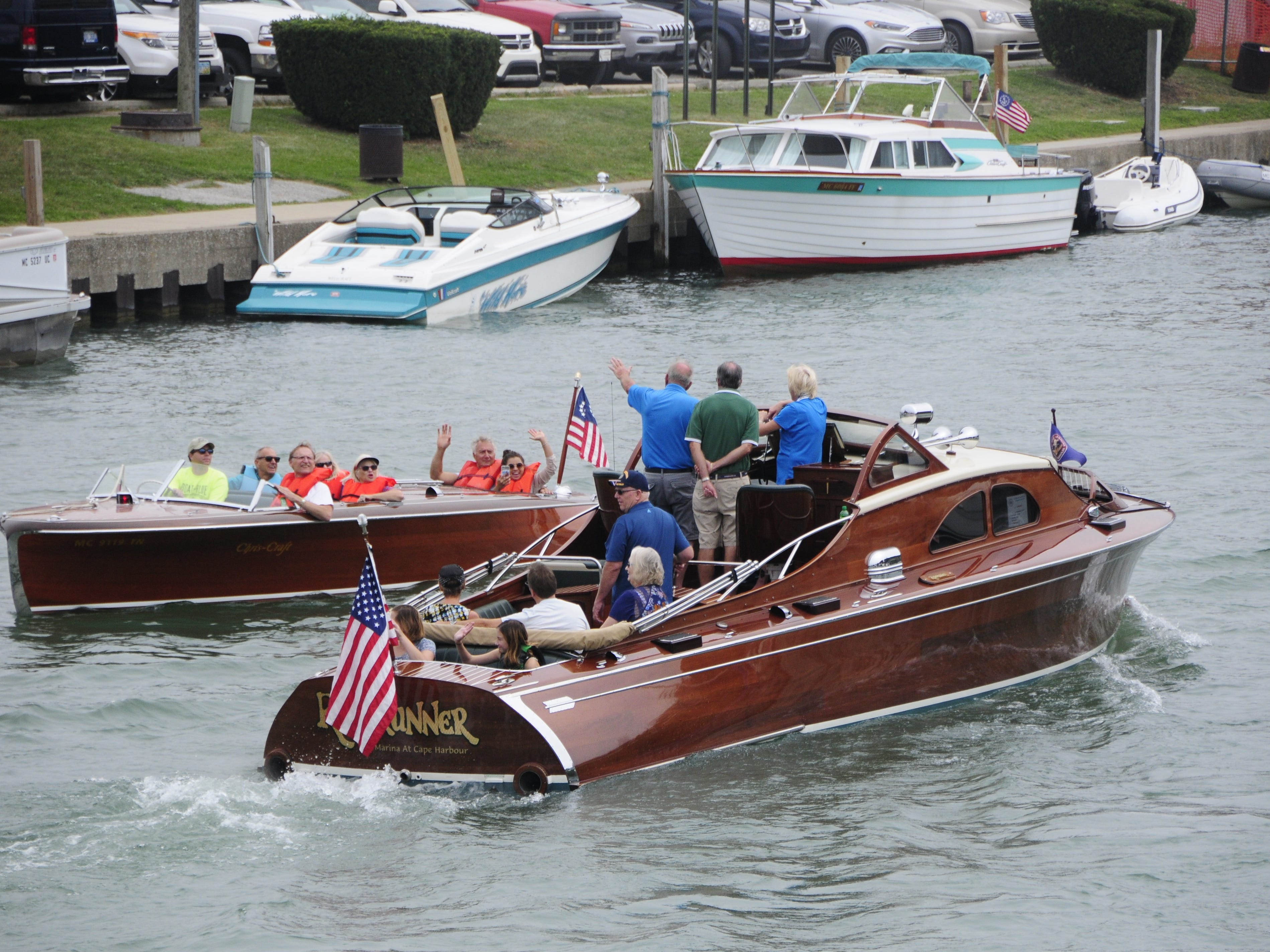 The Rumrunner passes another boat in the Black River during the Antique and Classic Boat Society International Boat Show on Saturday, Sept. 15, 2018.