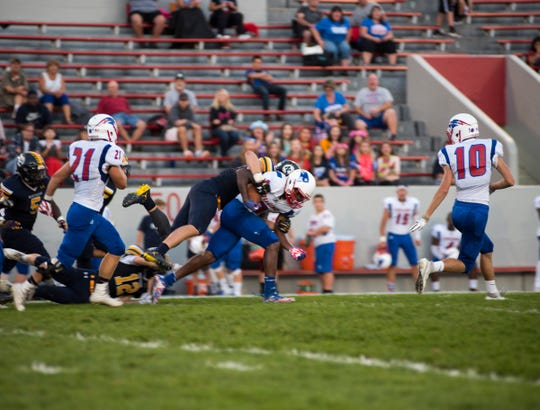 Port Huron Northern High School defensive back Braiden McGregor (back) takes down a player from Warren Cousino High School during their game Friday, Sept. 14, 2018 at Memorial Stadium.