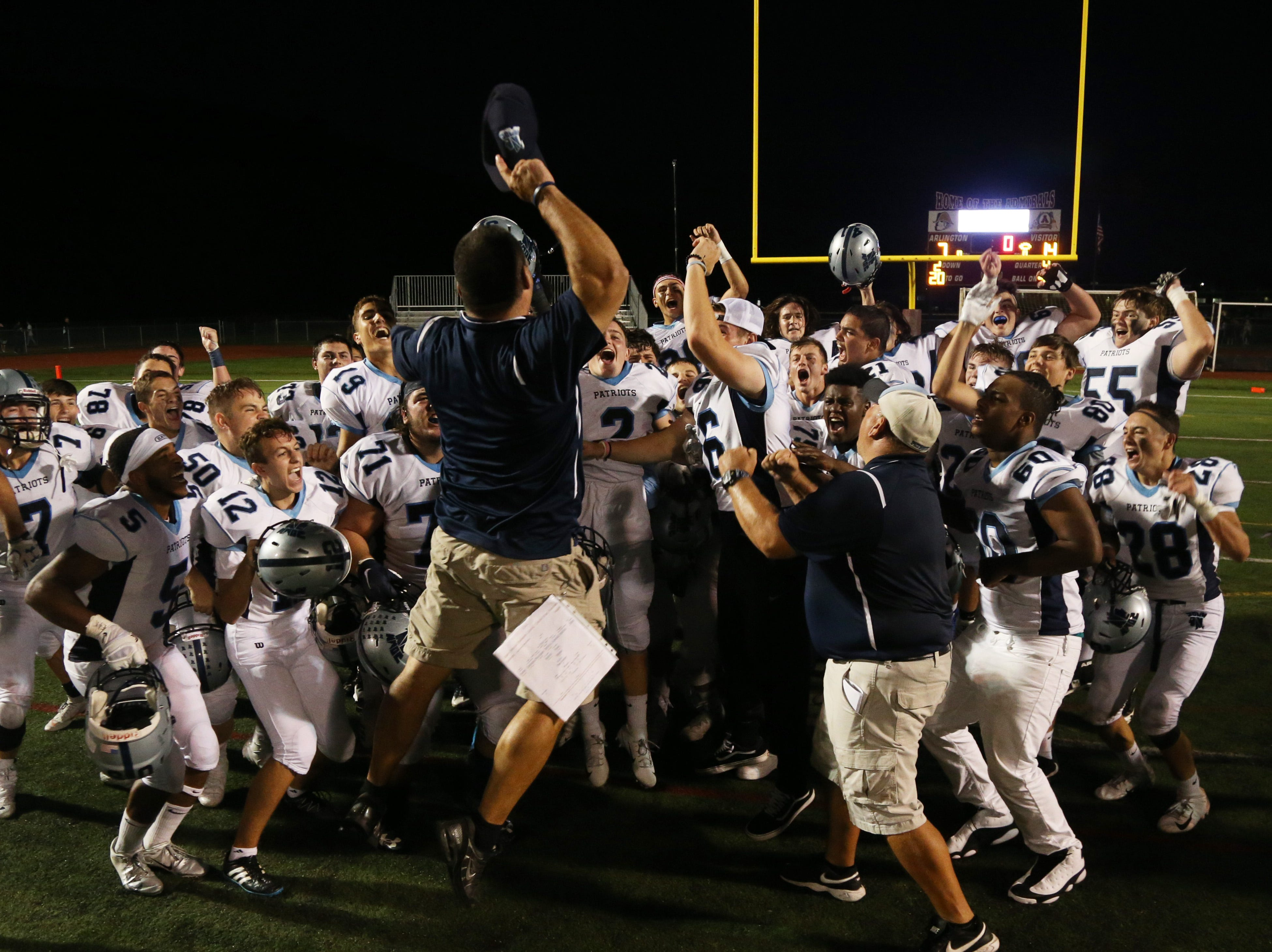 John Jay assistant coach Bob Schumacher leaps as he leads the cheer after the Patriots' comeback win over rival Arlington on Friday.