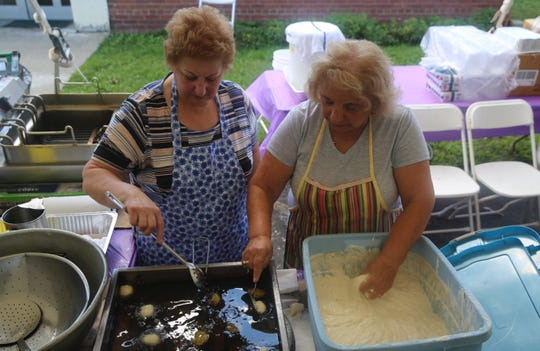From left, Kimisis Greek Orthodox Church members Anna Spyrou and Gloria Siderias prepare loukoumades at the church's Greek Festival on Saturday. Both said the dessert brings back childhood memories.