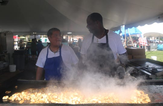 From right, Kimisis Greek Orthodox Church members Ronald Epps and Martin Hernandez have a conversation as Epps cooks chicken at the church's Greek Festival on Saturday. Dishes included gyros, baklava and loukoumades.