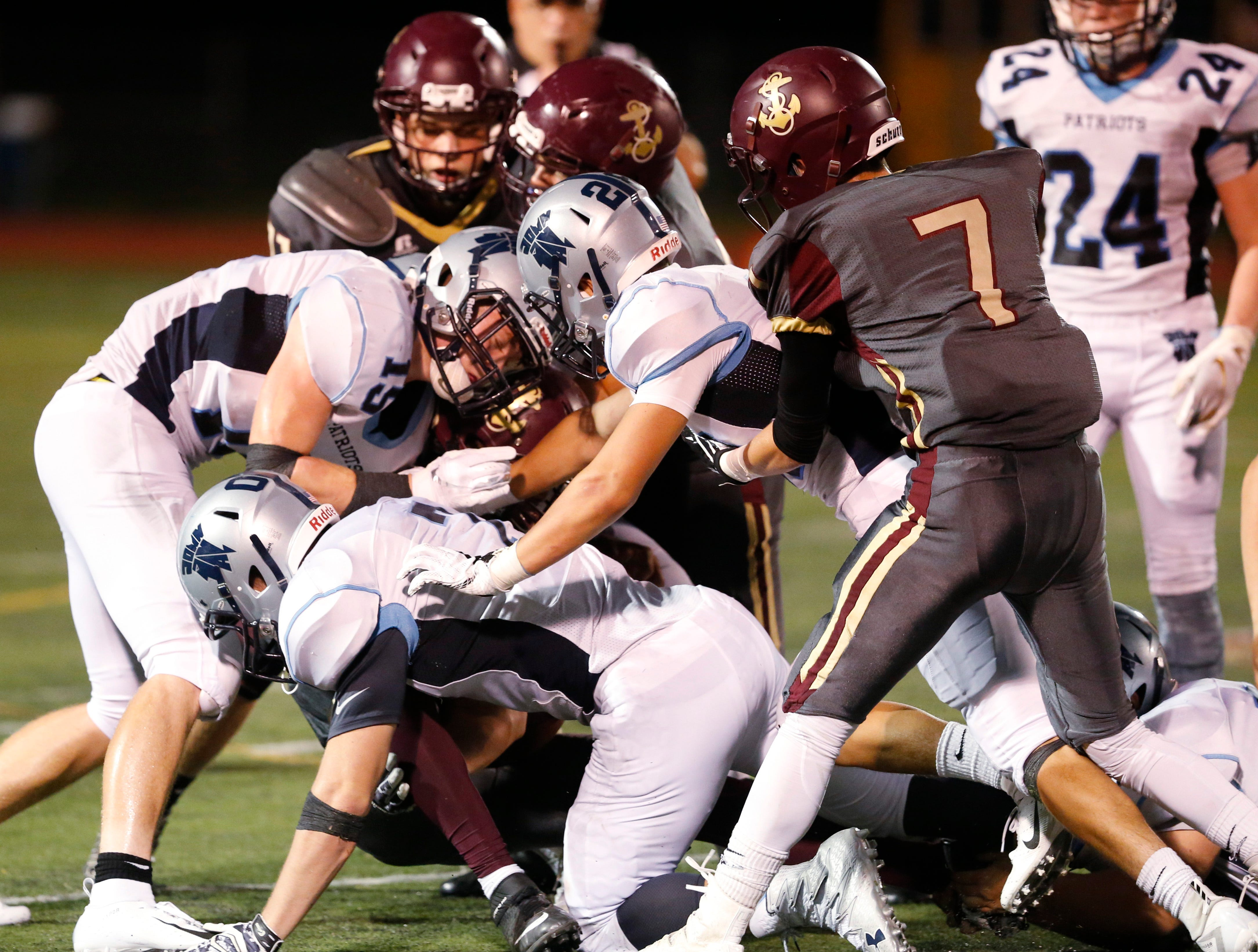 A group of John Jay defensive players converge on an Arlington ball carrier during a Sept. 14 game.