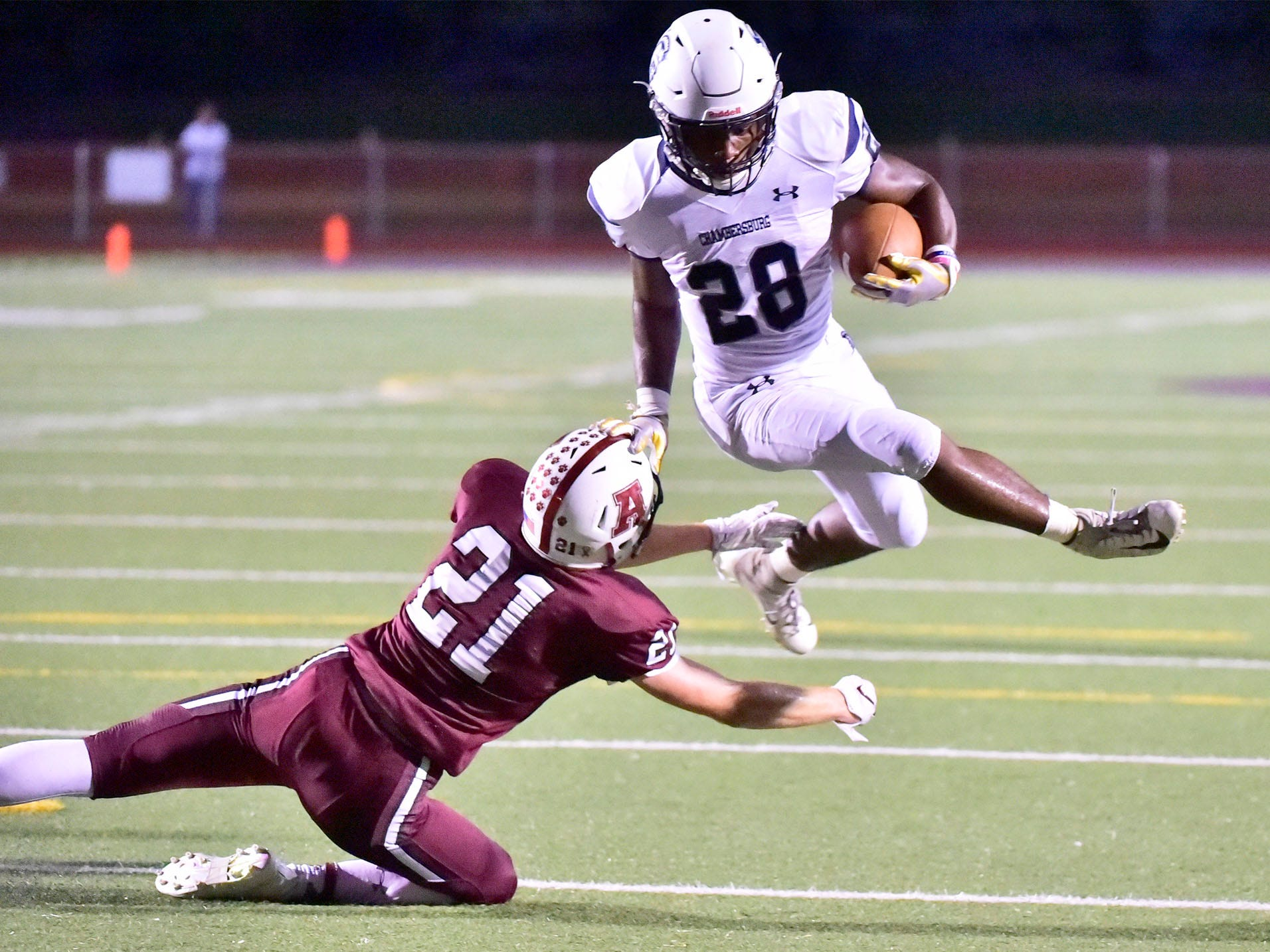 Chambersburg's Keyshawn Jones (28) leaps over Altoona's Connor Adams (21) to score for the Trojans. Chambersburg defeated Altoona 48-28 in PIAA football to move to 4-0 on Friday, Sept. 14, 2018.