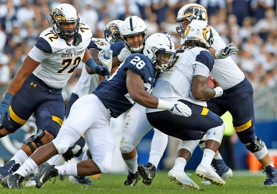 Penn State's Jayson Oweh (28) sacks Kent State quarterback Woody Barrett (15) during the second half of an NCAA college football game in State College, Pa., Saturday, Sept. 15, 2018. Penn State won 63-10.
