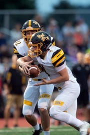 Red Lion quarterback Zach Mentzer (12) hands the ball off to Tyler Ness (4) during a game at Central York on Friday, September 14, 2018. The Red Lion Lions beat the Central York Panthers, 56-28.