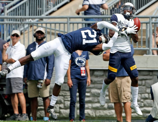 Kent State's Mike Carrigan (87) hauls in a pass and runs it in for a touchdown as Penn State's Amani Oruwariye (21) defends during the first half of an NCAA college football game in State College, Pa., Saturday, Sept. 15, 2018.