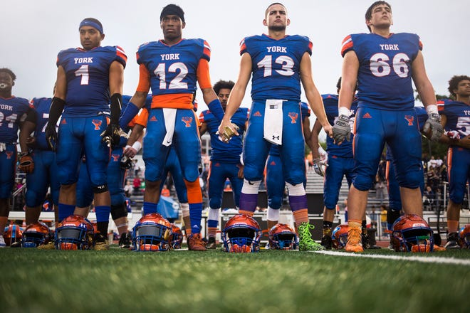 York High players, from left, Dayjure Stewart, Rob Rideout, Seth Bernstein, and  Trey Bernstein, stand during the national anthem prior to the game. York High defeats New Oxford 71-14 in football at Small Athletic Field in York, Friday, September 14, 2018.