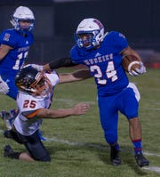 Reno's Anthony Hill straight-arms Douglases Brady Dufloth in their football game at Reno High School on Friday night, Sept. 14, 2018.