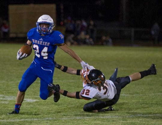 Reno's Anthony Hill gets away from Douglas' Andrew Wilken in their football game at Reno High School on Friday night, Sept. 14, 2018.